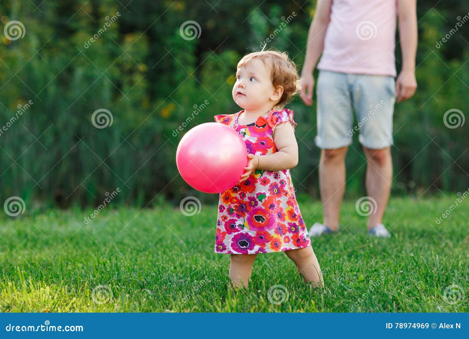 Μικρό κορίτσι στο πάρκο με τη σφαίρα στα χέρια