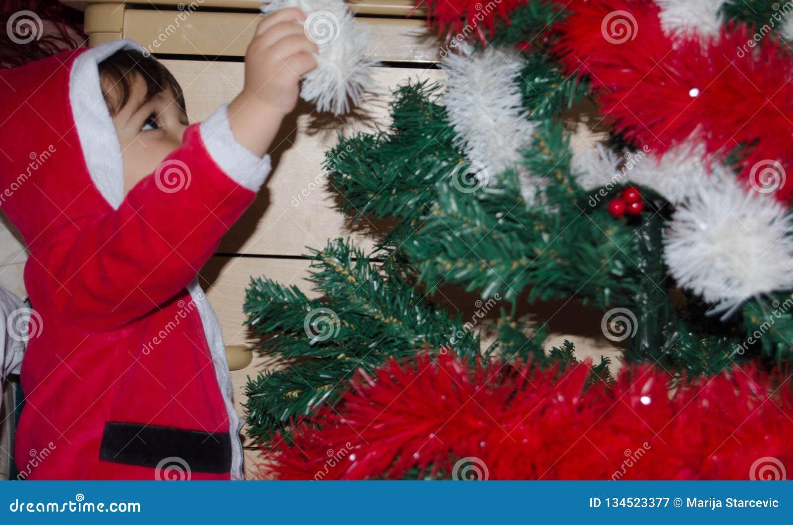 Μικρό παιδί που βάζει τη διακόσμηση Χριστουγέννων στο χριστουγεννιάτικο δέντρο