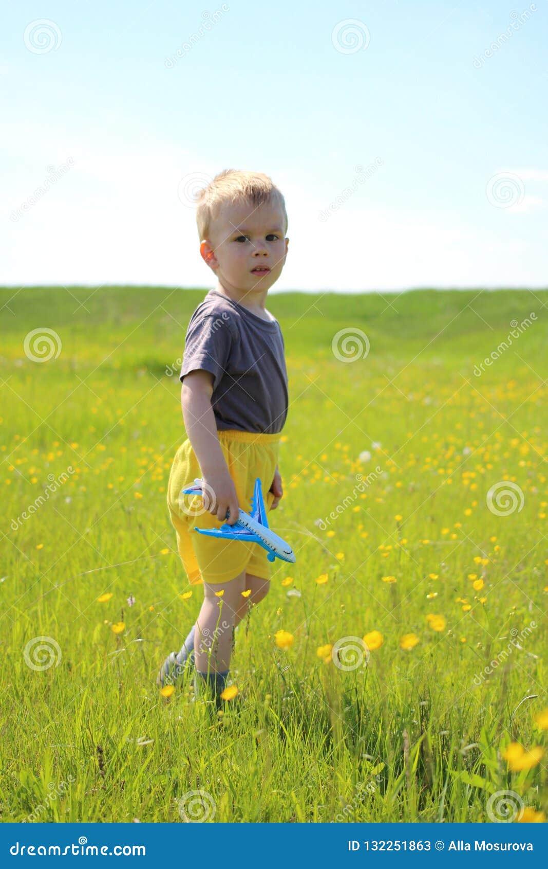Μικρό παιδί που περπατά στο λιβάδι με ένα αεροπλάνο παιχνιδιών