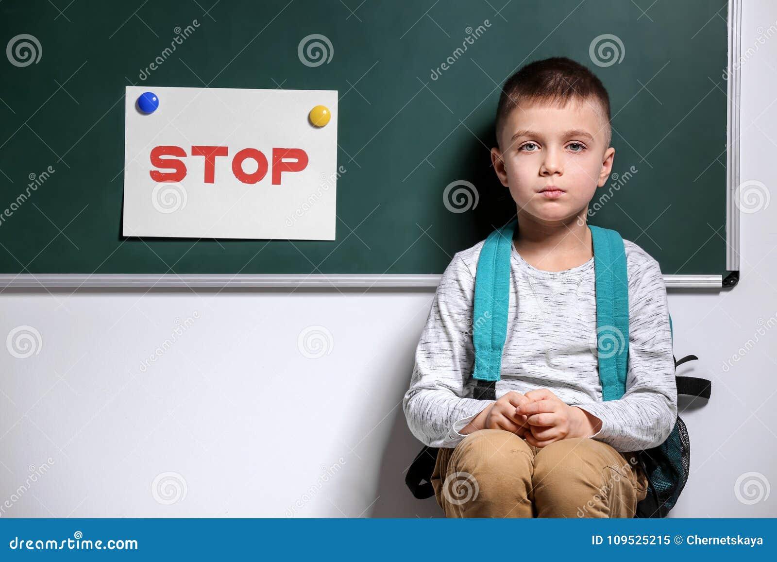 Μικρό παιδί που φοβερίζεται στο σχολείο κοντά στον πίνακα κιμωλίας