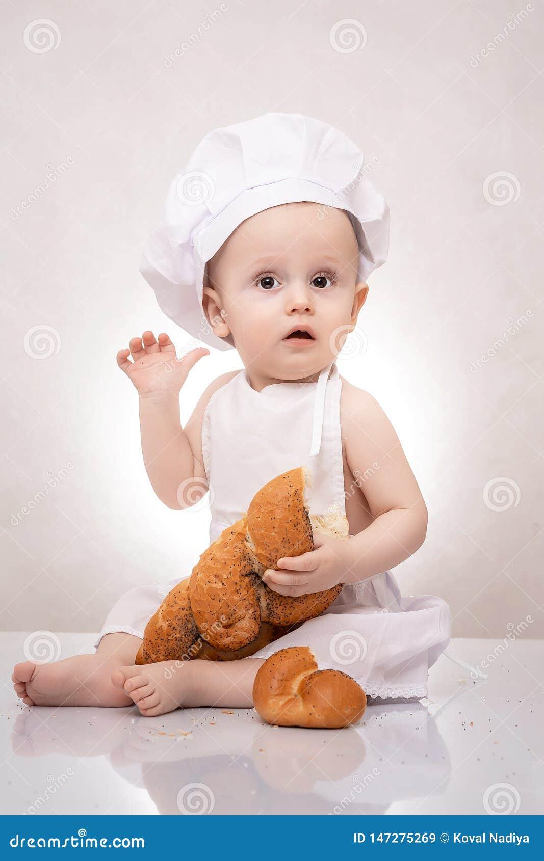 Μικρό παιδί στο κοστούμι μαγείρων με το ψωμί να γελάσει ευτυχώς