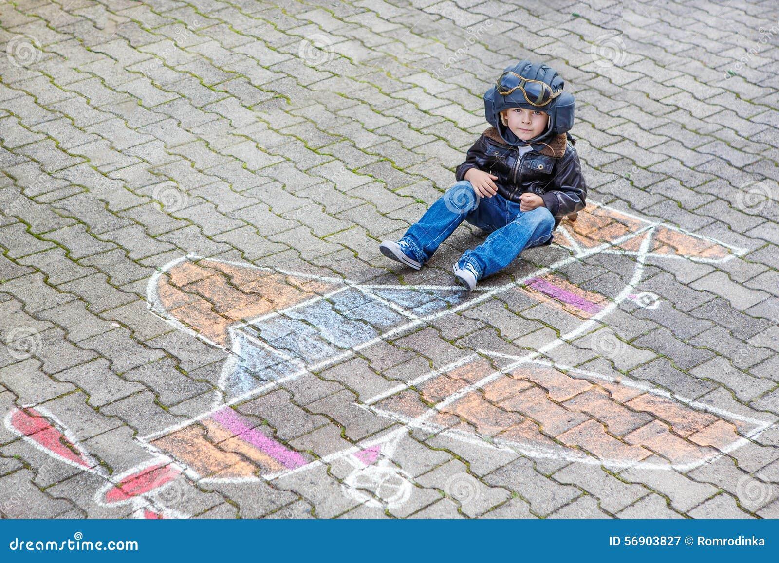Μικρό παιδί που έχει τη διασκέδαση με το σχέδιο εικόνων αεροπλάνων με την κιμωλία