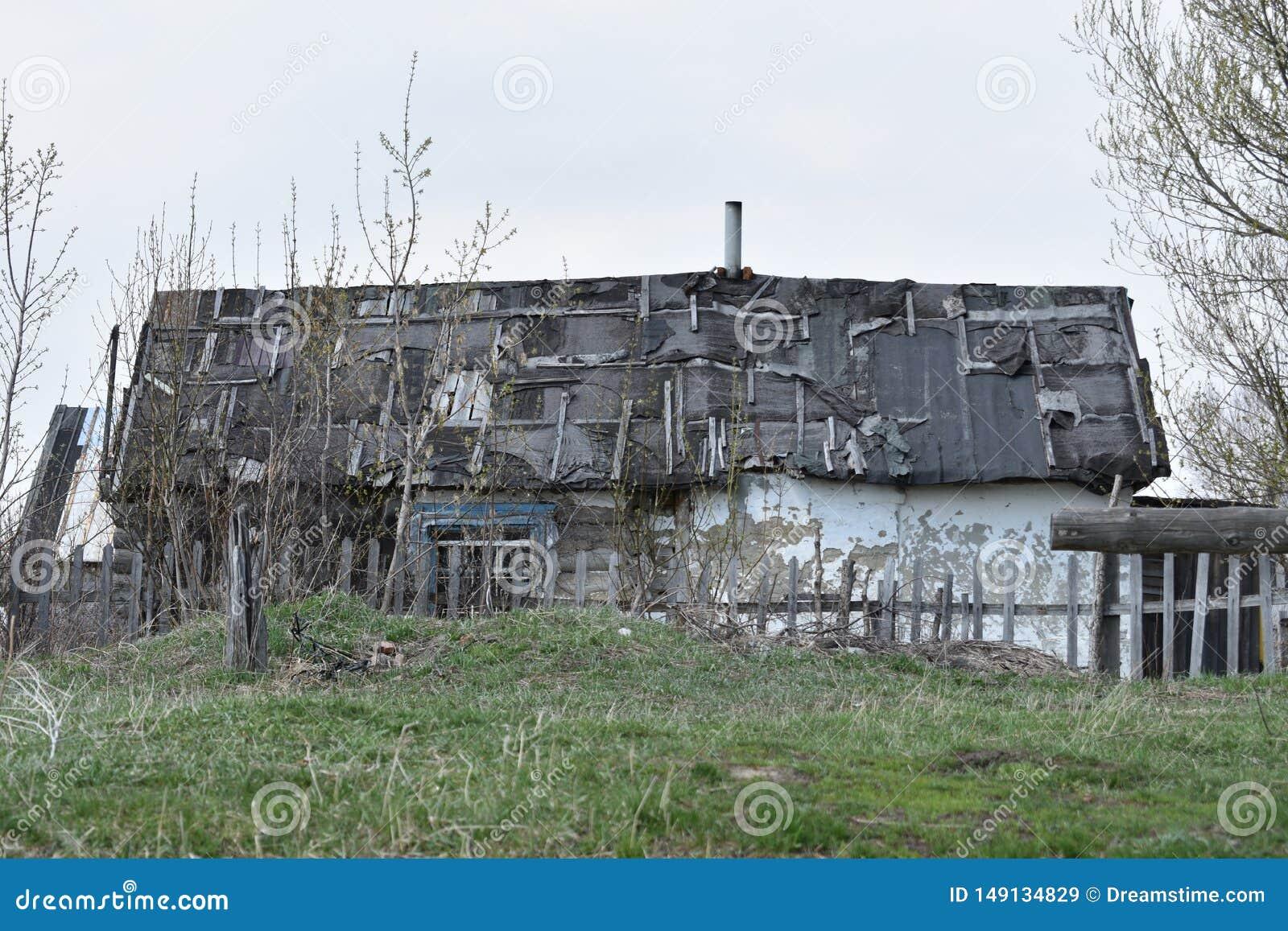 Μικρό παλαιό σπίτι με μια leaky στέγη