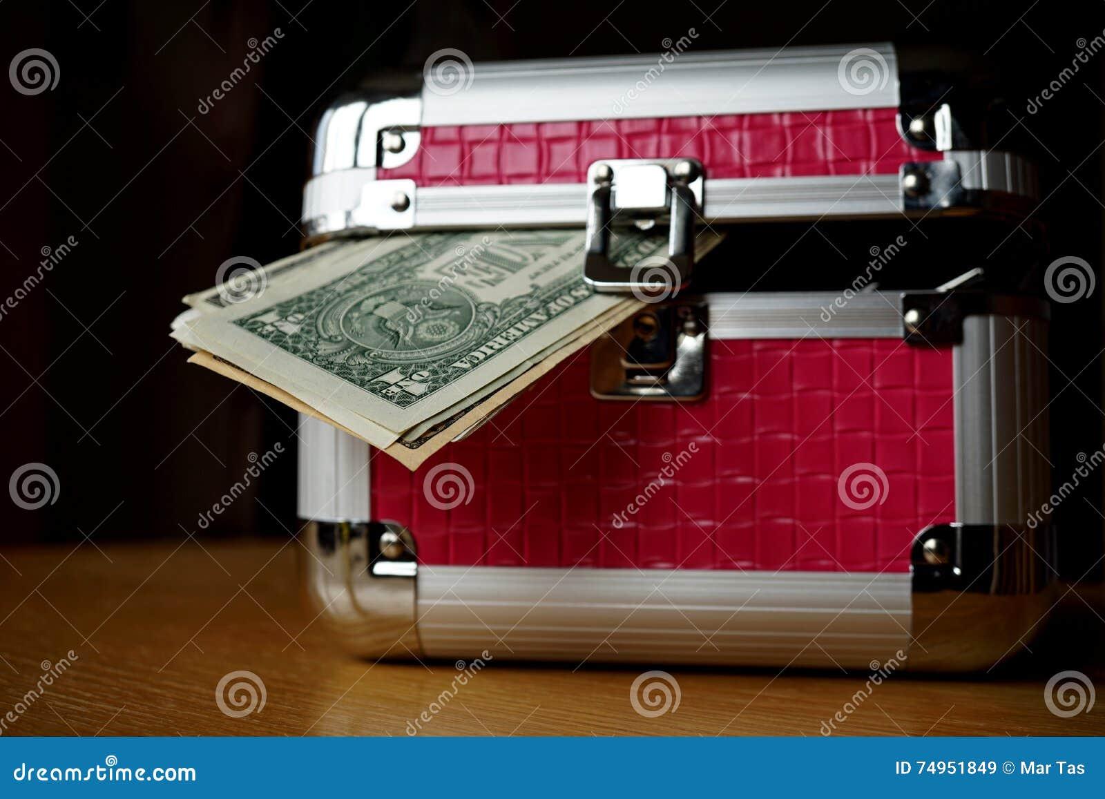 Μικρό ρόδινο strongbox με τις ασημένιες άκρες που κρατούν το παχύ πακέτο των χρημάτων (αμερικανικά δολάρια, Δολ ΗΠΑ)