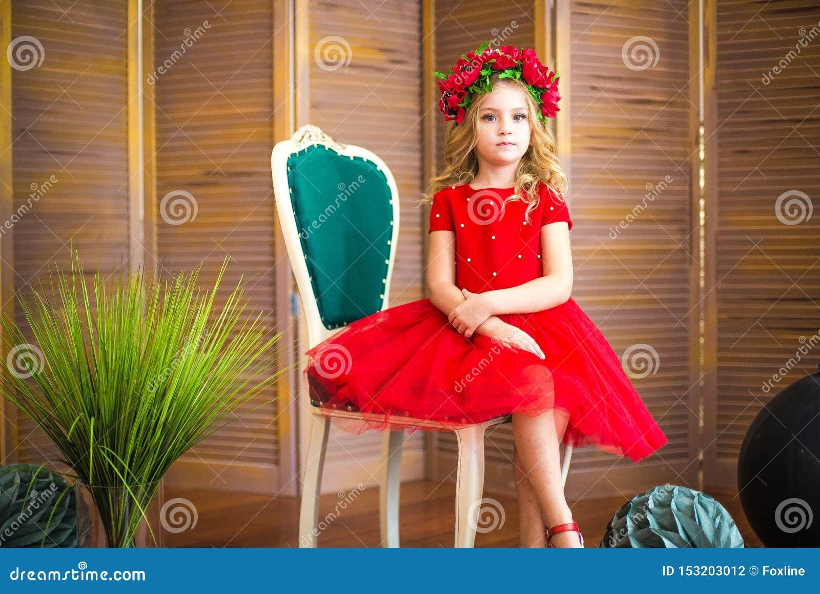 Μικρό χαμόγελο κοριτσιών, μόδα Παιδί που χαμογελά με το ξανθό hairstyle στο κόκκινο φόρεμα Έννοια σαλονιών ομορφιάς Haircare, κομ