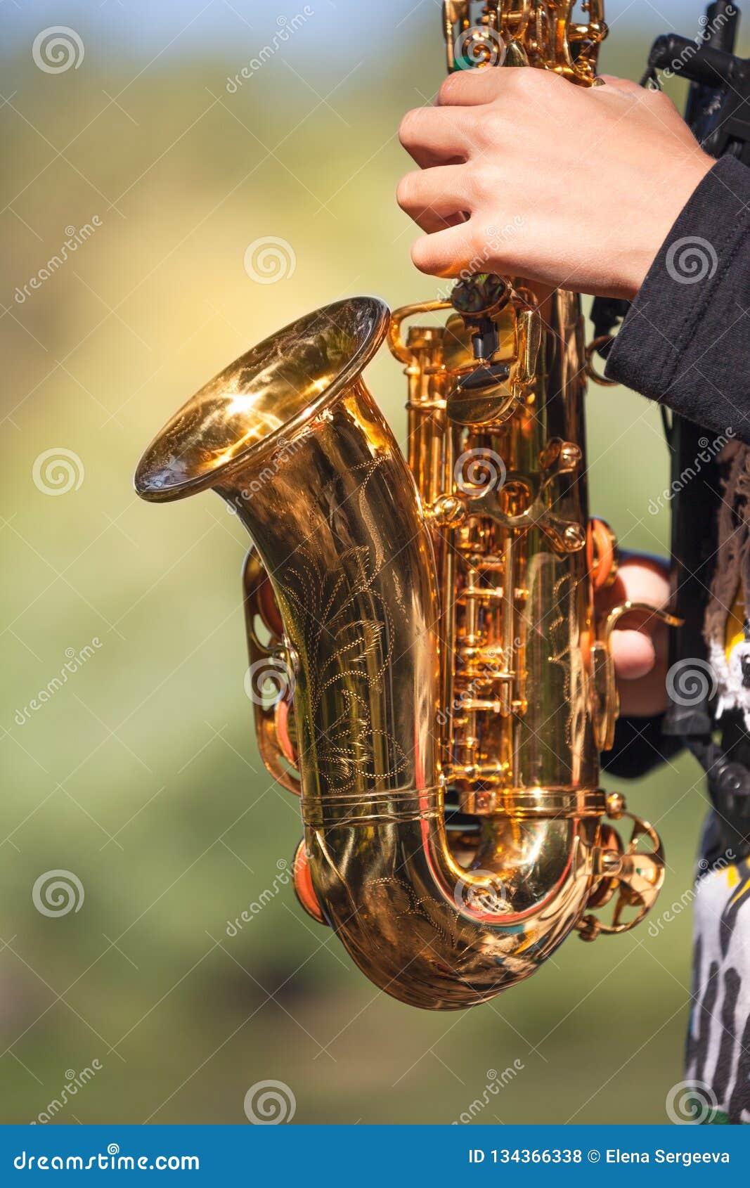 Μικρό χρυσό saxophone στα χέρια