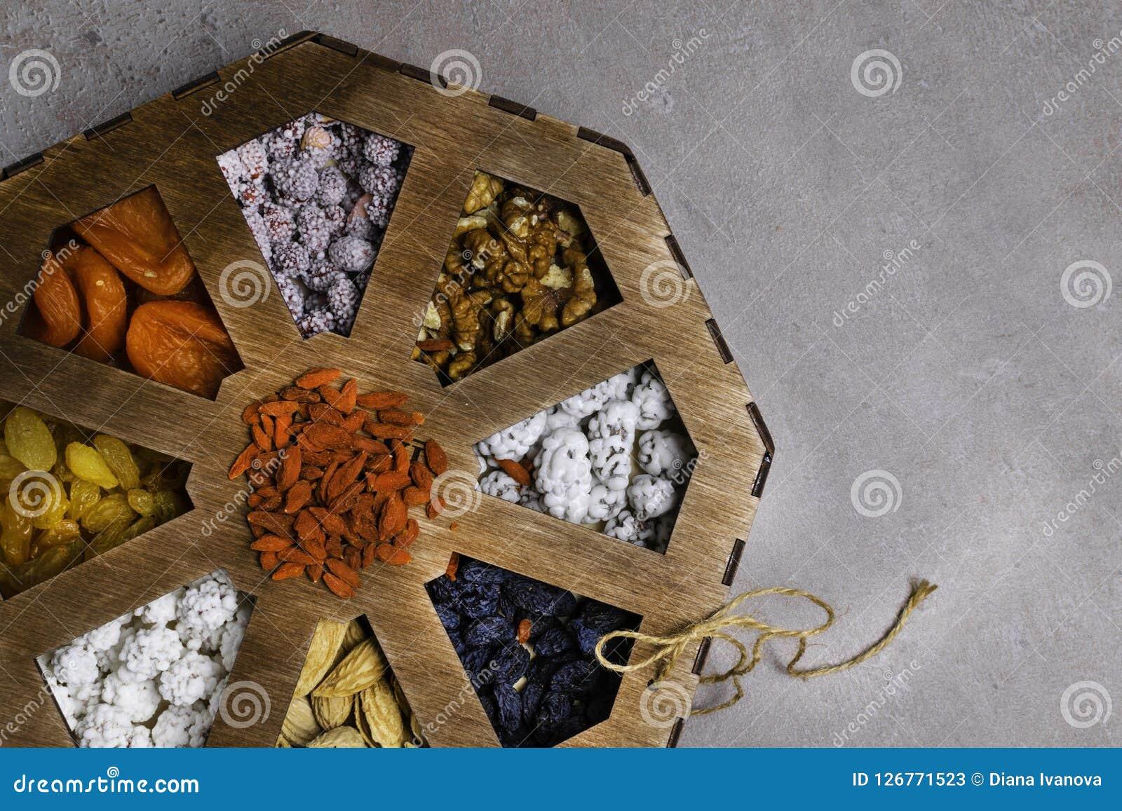 Μικτά καρύδια σε ένα γκρίζο υπόβαθρο στο ξύλινο κιβώτιο Υγιή τρόφιμα και πρόχειρο φαγητό Τοπ όψη