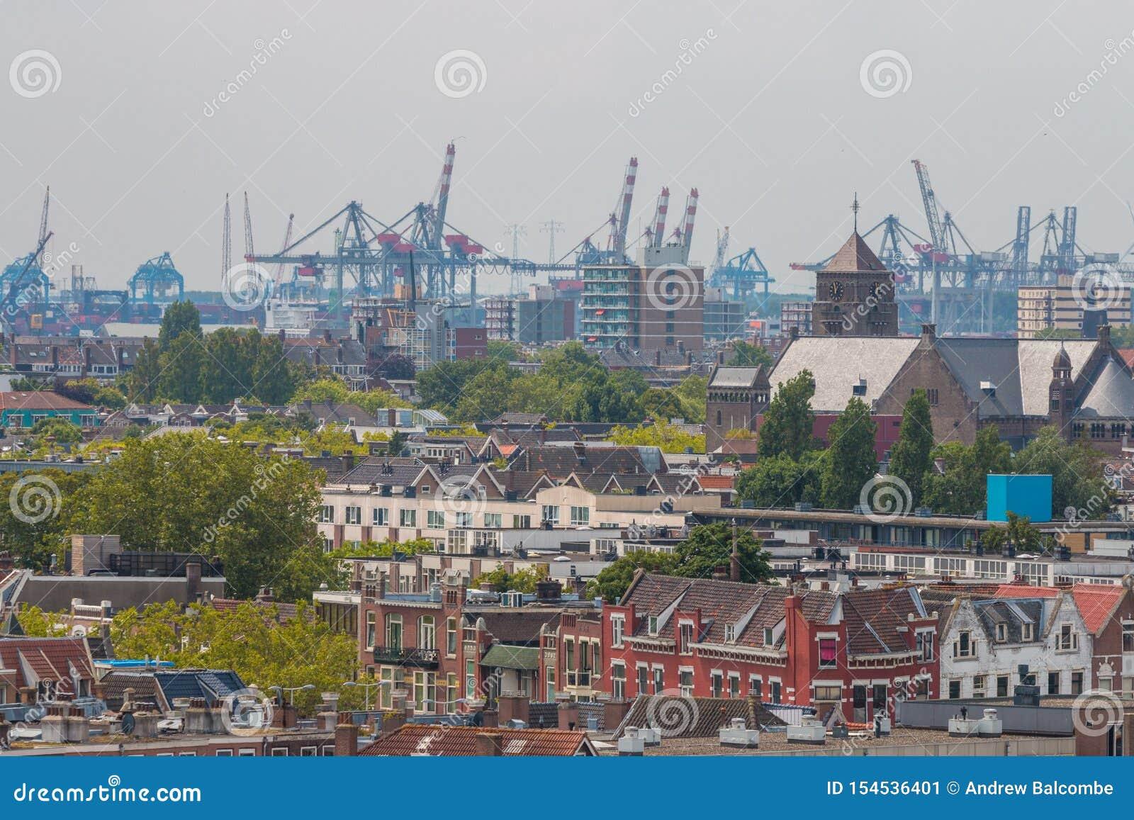 Μικτή κλασική αρχιτεκτονική των φυλλωδών αστικών πολυκατοικιών του Ρότερνταμ στο πρώτο πλάνο με τους γερανούς λιμένων λιμενικών π