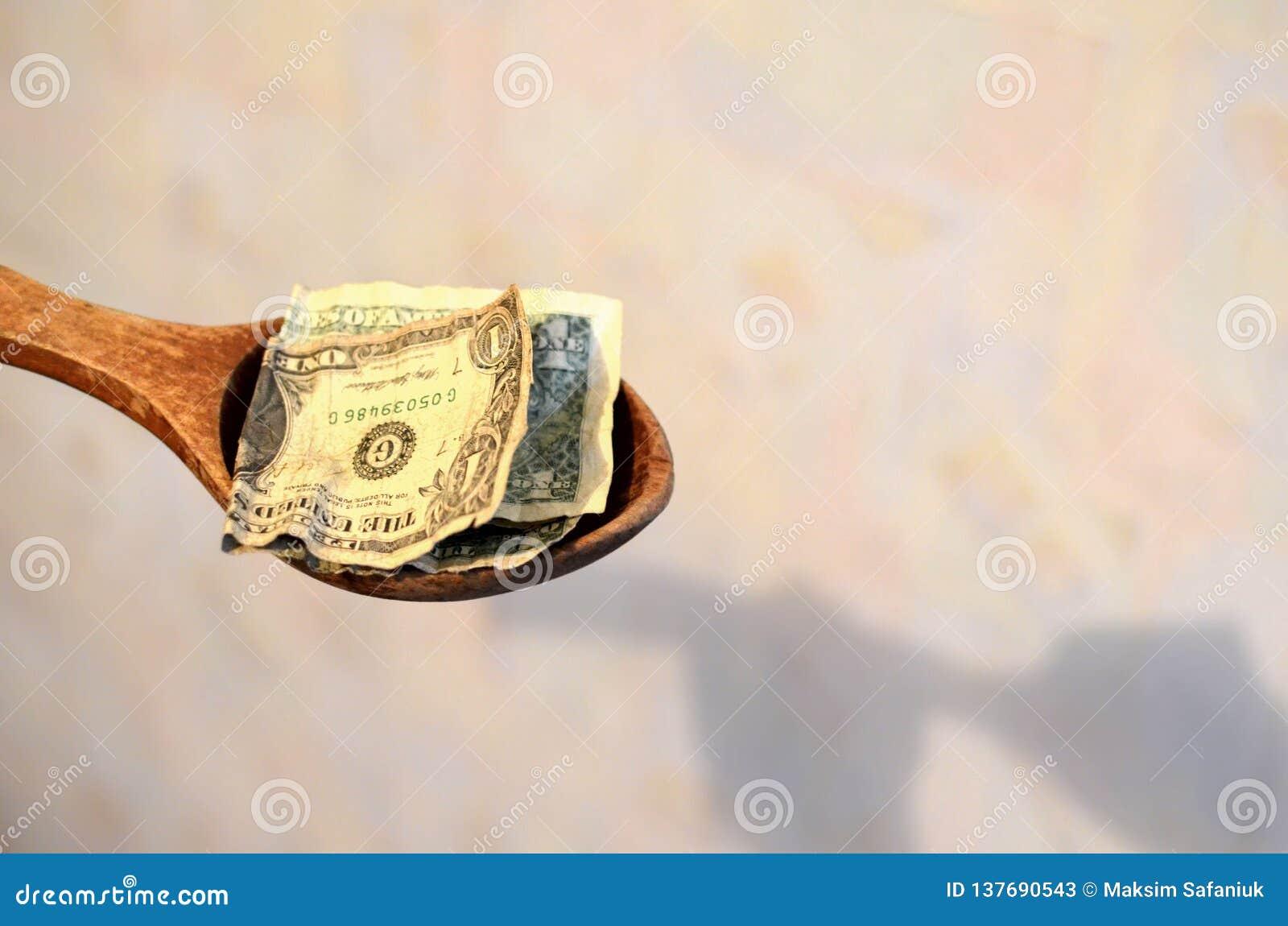 μισθός Αμερικανικοί λογαριασμοί, δολάρια σε ένα ξύλινο κουτάλι