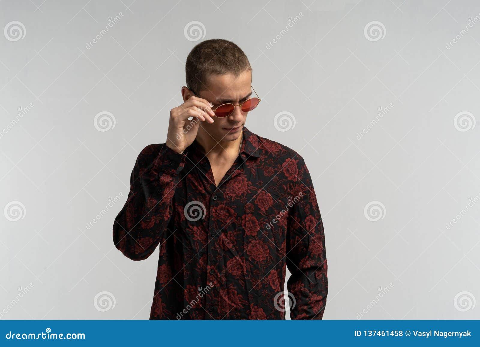 Μισό πορτρέτο μήκους του μοντέρνου όμορφου νεαρού άνδρα που απομονώνεται στο άσπρο υπόβαθρο