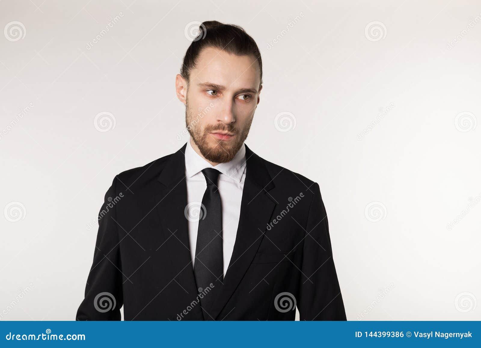 Μισό πορτρέτο μήκους του όμορφου γενειοφόρου τύπου brunette με το καθιερώνον τη μόδα hairdo στο μαύρο κοστούμι