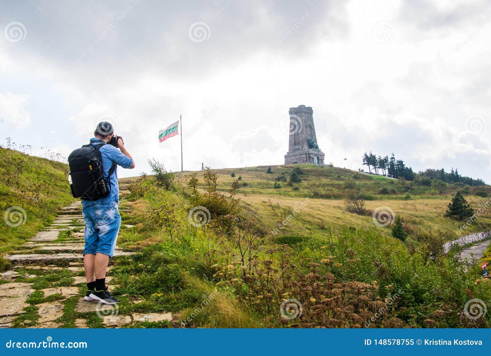 Μνημείο Shipka με μια βουλγαρική σημαία και έναν φωτογράφο, τουρίστας