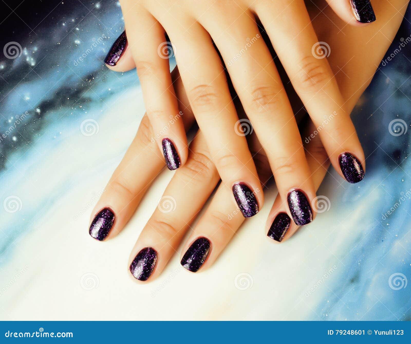 Μοντέρνη έννοια μανικιούρ: τα δάχτυλα γυναικών με την πορφύρα καρφιών ακτινοβολούν στα καρφιά όπως τον κόσμο, υπόβαθρο κόσμου