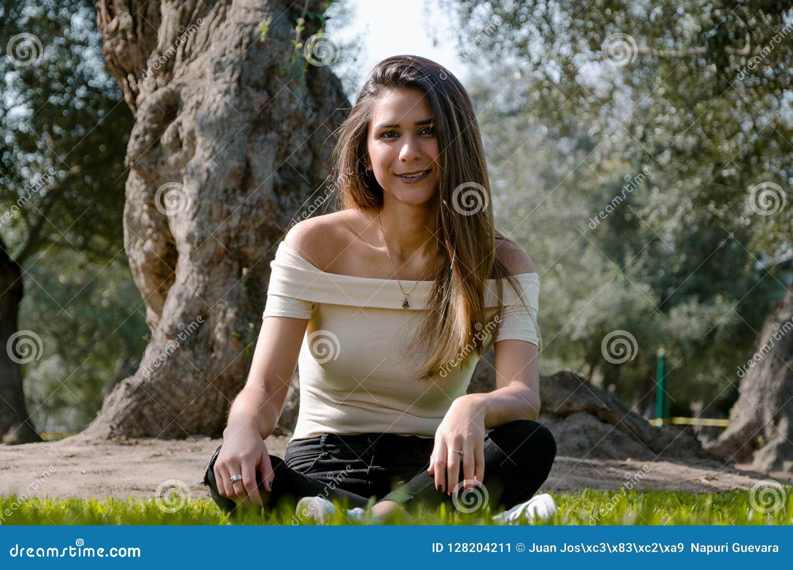 Μοντέρνη εύθυμη συνεδρίαση brunette κάτω από ένα δέντρο σε ένα πάρκο