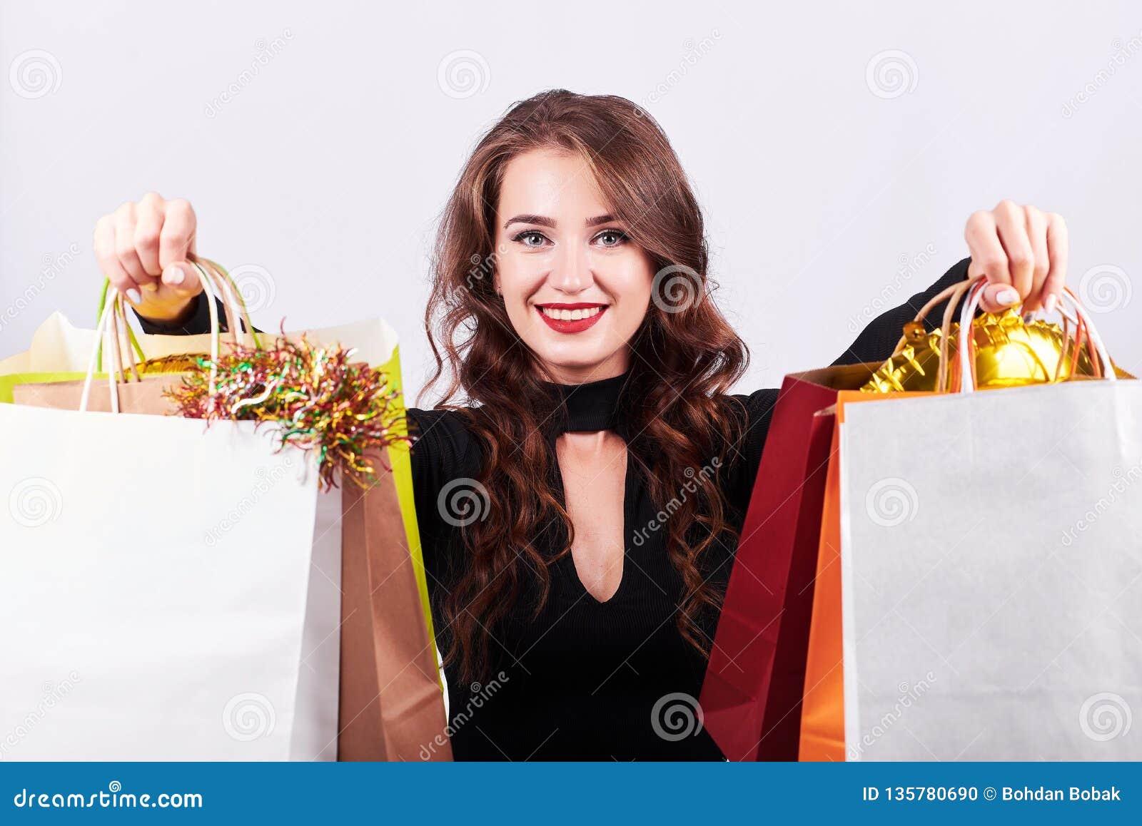 Μοντέρνη νέα γυναίκα brunette που κρατά τις ζωηρόχρωμες τσάντες αγορών