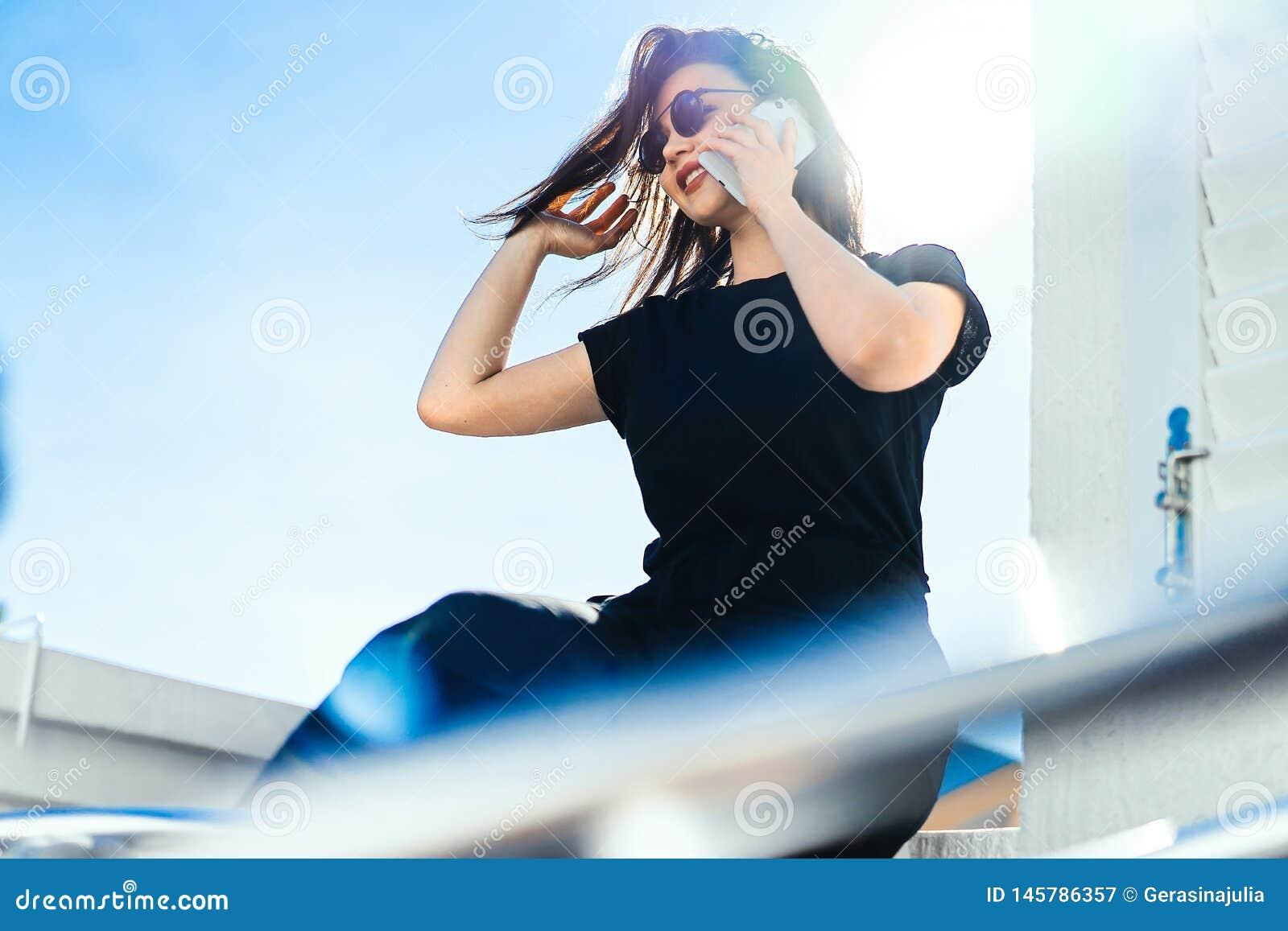 Μοντέρνη νέα συνεδρίαση γυναικών υπαίθρια στο μπαλκόνι και ομιλία με κινητό τηλέφωνο