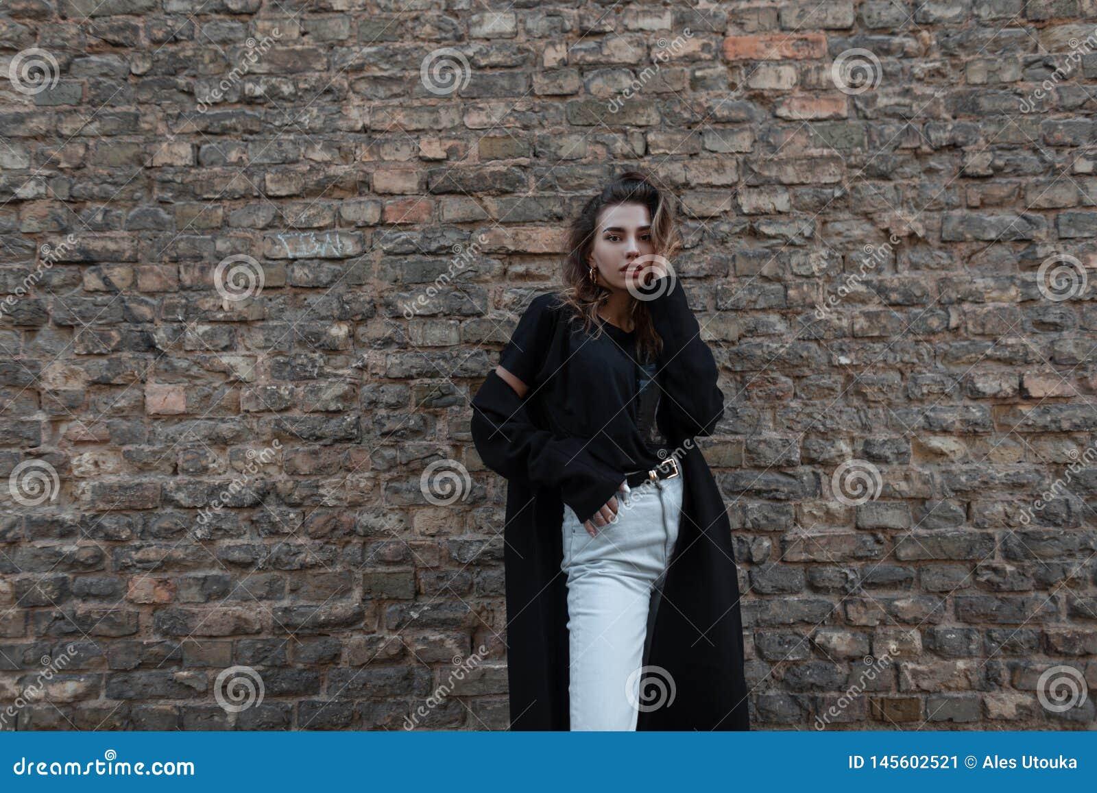 Μοντέρνη σύγχρονη νέα γυναίκα brunette σε ένα μαύρο κομψό μακρύ παλτό σε μια μοντέρνη μπλούζα στην άσπρη τοποθέτηση τζιν