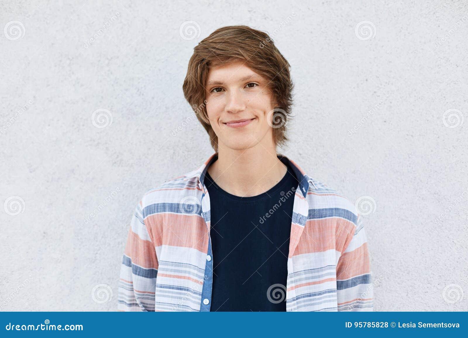Μοντέρνος έφηβος με το καθιερώνον τη μόδα hairstyle που έχει τα σκοτεινά μάτια, το καθαρά δέρμα και τα λακκάκια στα μάγουλα που φ