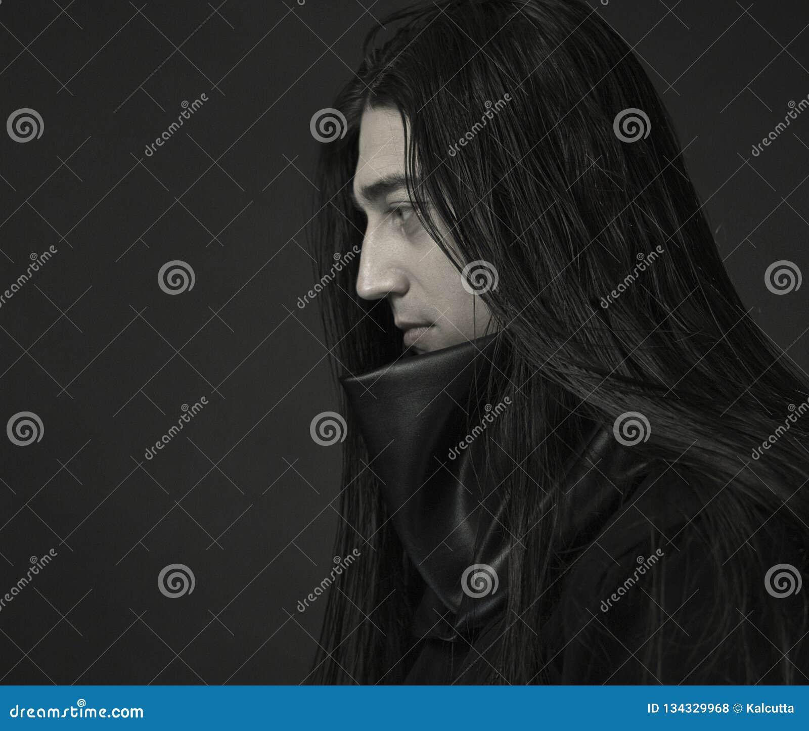 Μοντέρνος όμορφος νεαρός άνδρας Καυκάσιο ανθρώπινο πορτρέτο άτομο στα μαύρα ενδύματα με σκοτεινό μακρυμάλλη