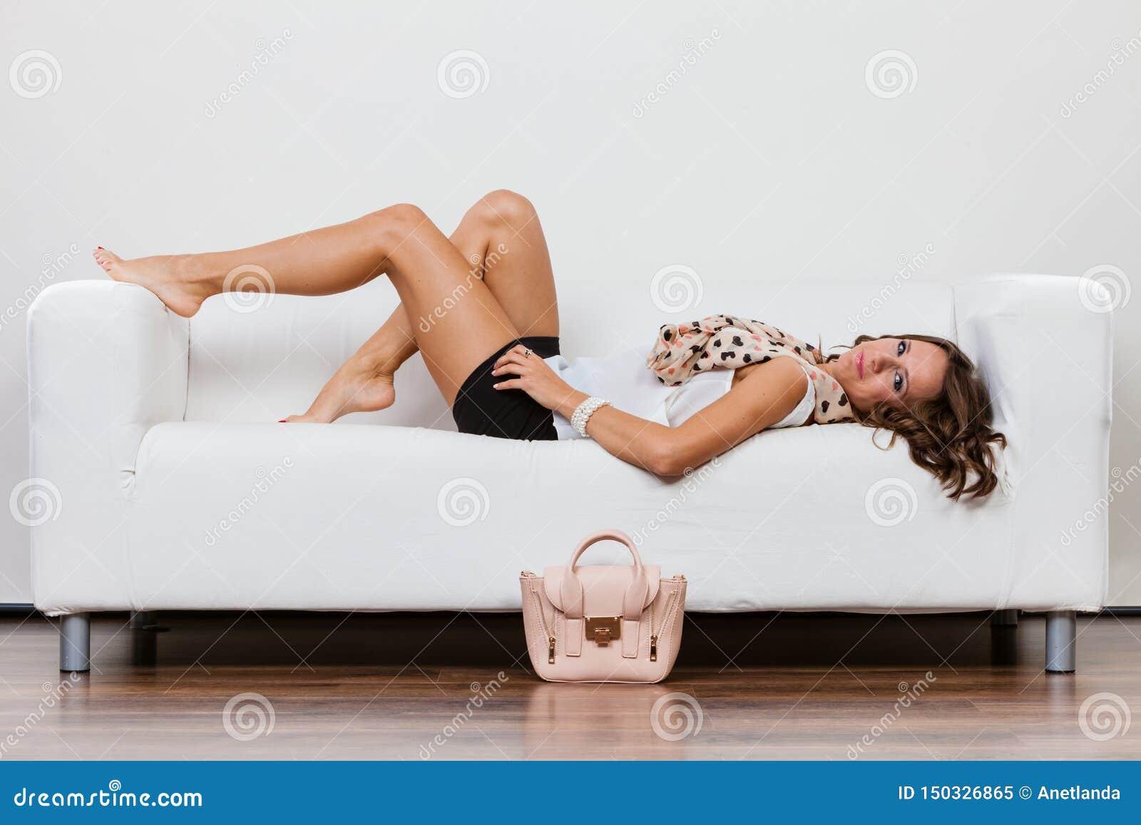 Μοντέρνο κορίτσι με την τσάντα που βρίσκεται στον καναπέ