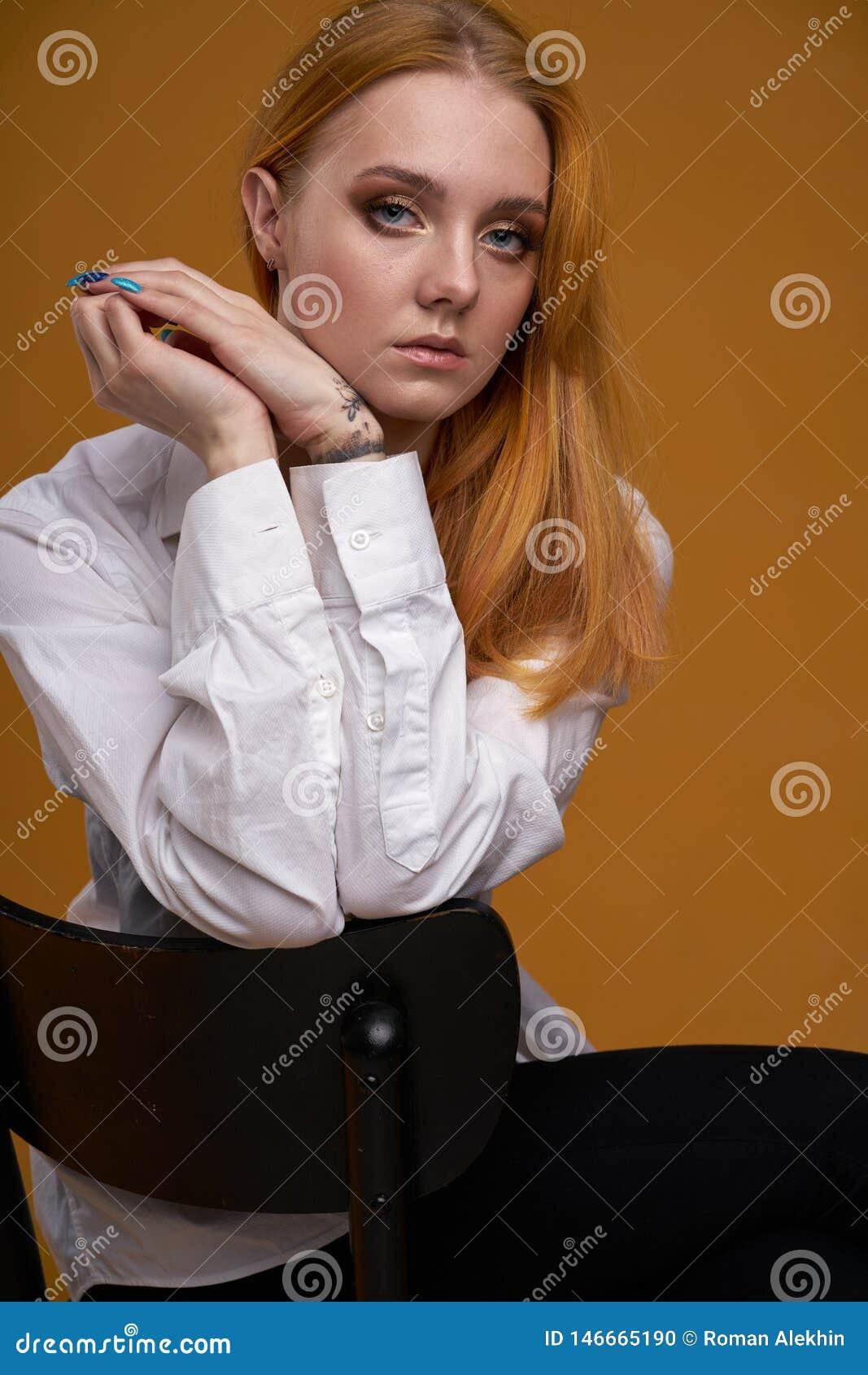 Μοντέρνο νέο κορίτσι με τη σγουρή τρίχα, που χαμογελά cutely, που θέτει, στο κίτρινο υπόβαθρο