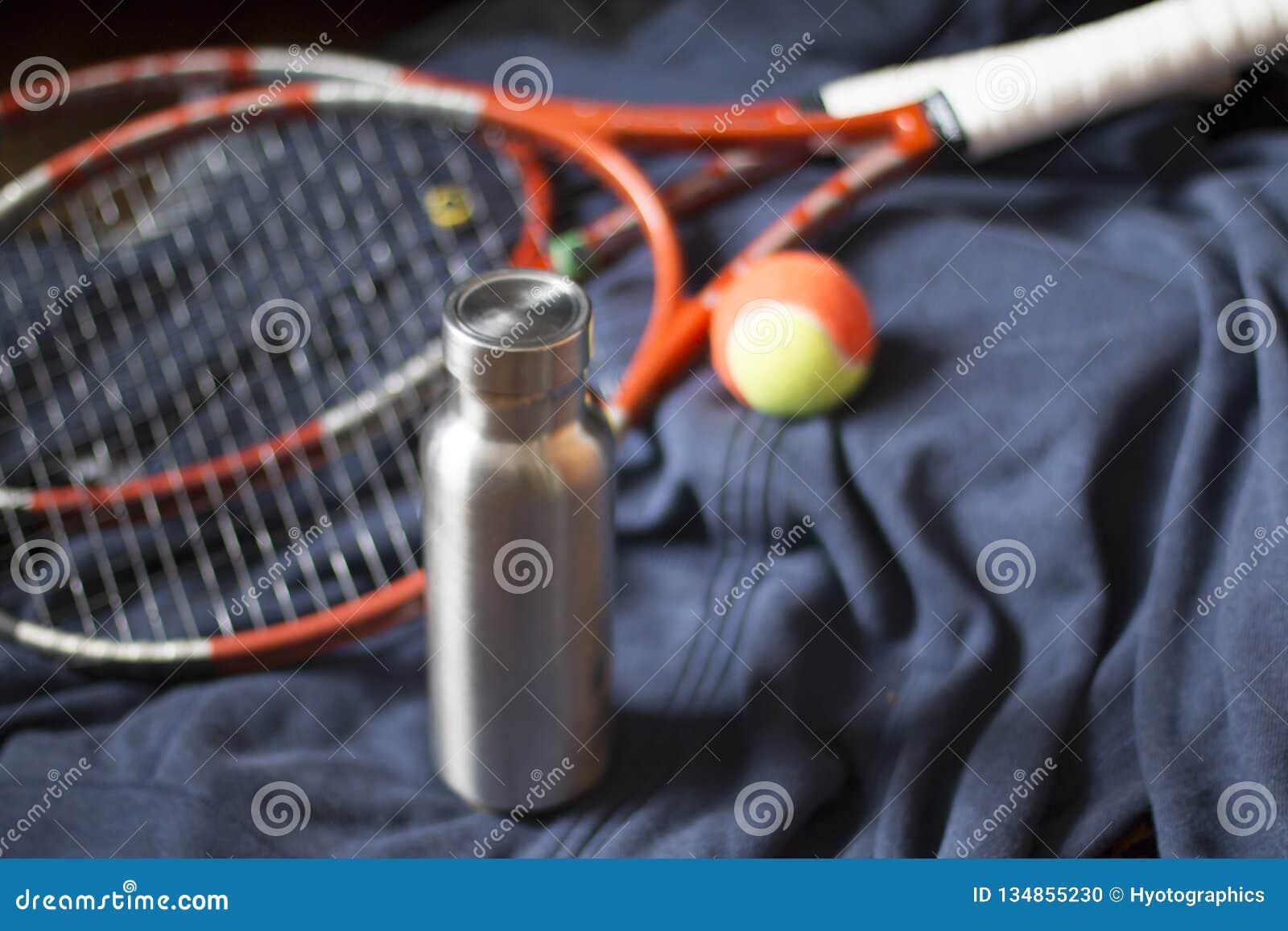 Μονωμένο ανοξείδωτο μπουκάλι με τη ρακέτα και τη σφαίρα αντισφαίρισης