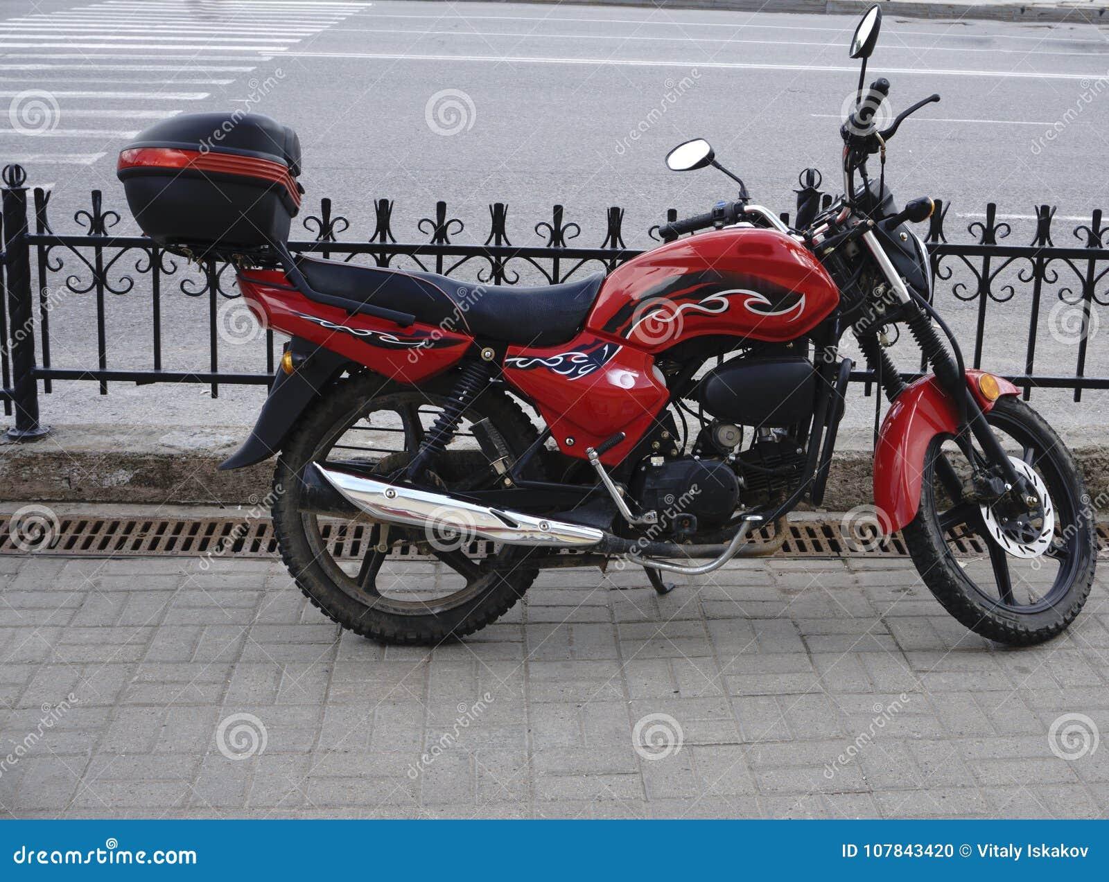 Μοτοσικλέτα με μια κόκκινη απόχρωση και ένα δροσερό υπόβαθρο