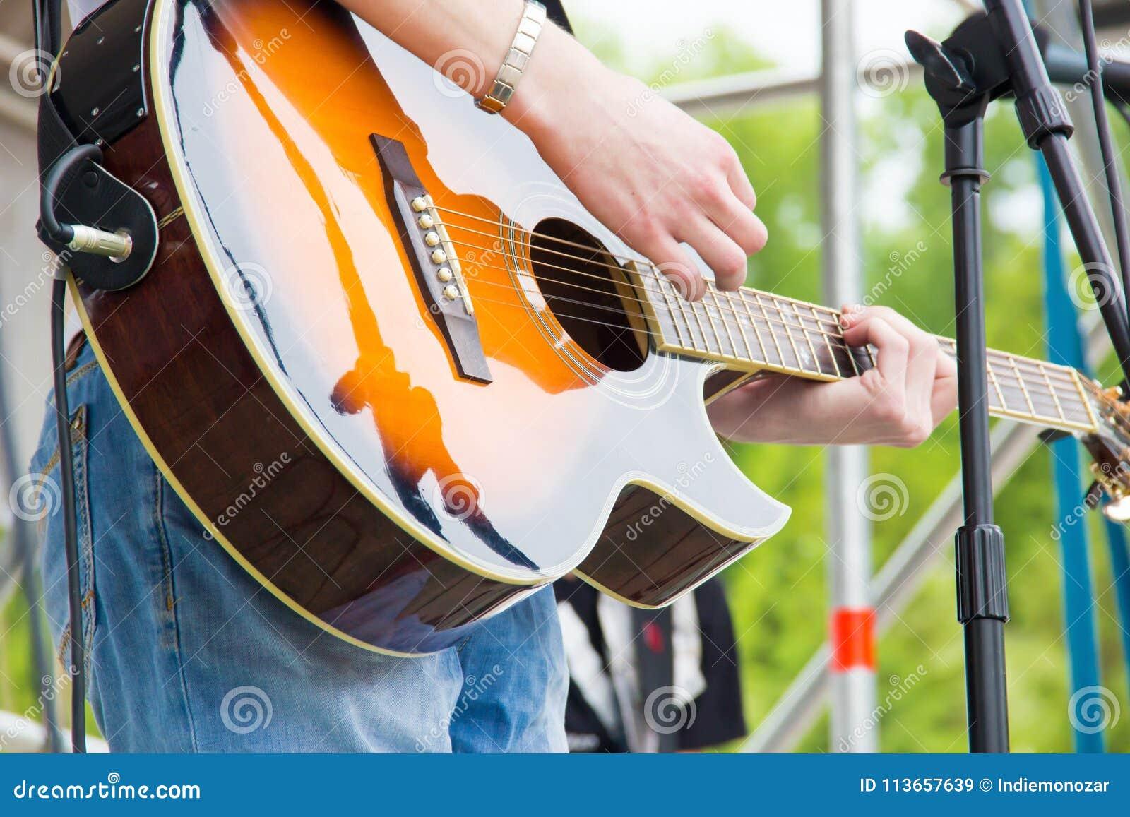 Μουσική ζώνη perfom σε ένα υπαίθριο φεστιβάλ Ακουστική κιθάρα χρώματος ηλιοφάνειας μουσικής παιχνιδιού ατόμων κιθαριστών