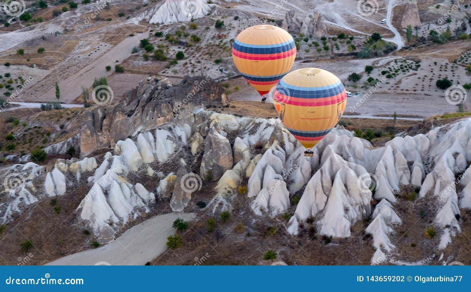 Μπαλόνια ζεστού αέρα που αιωρούνται πέρα από την ηφαιστειακή κοιλάδα Μουσείο διαβίωσης, Cappadocia, Τουρκία, φθινόπωρο