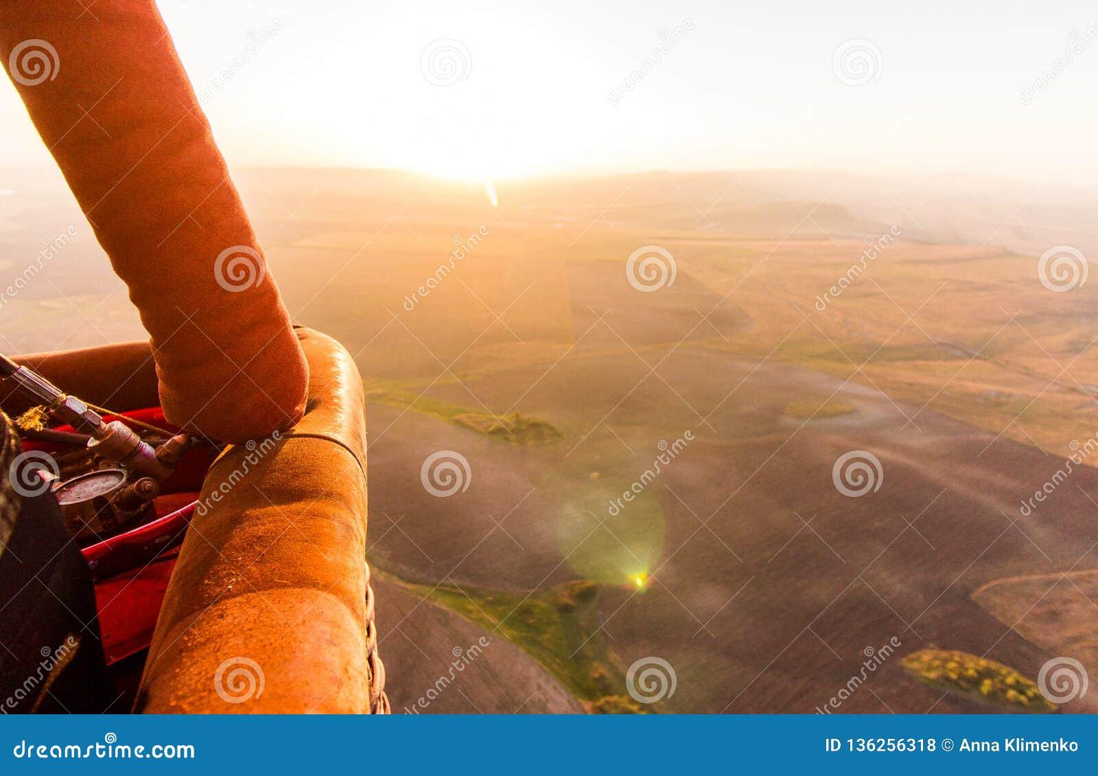 Μπαλόνι ζεστού αέρα busket κατά τη διάρκεια της ανατολής που πετά πέρα από την κοιλάδα
