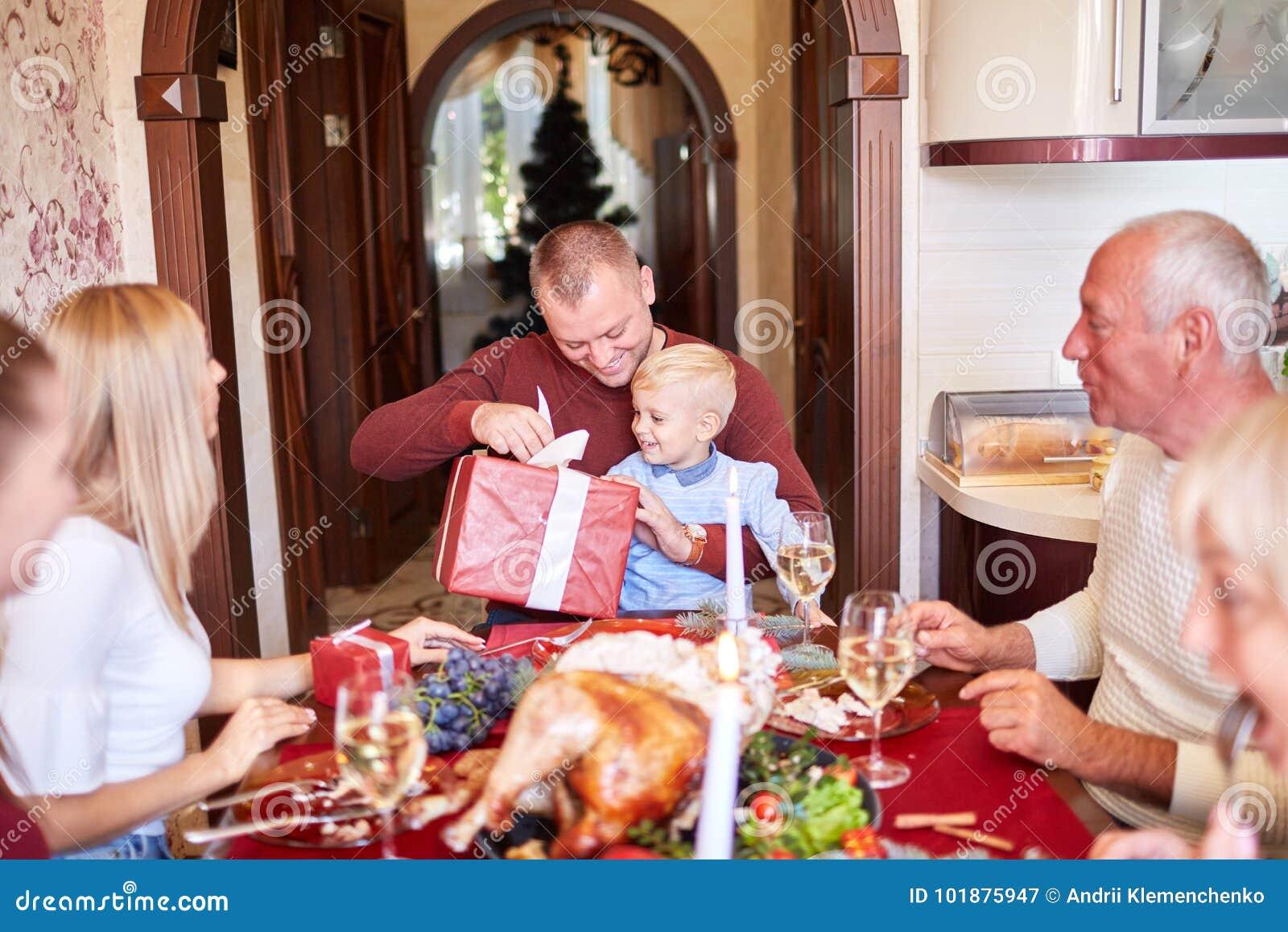 Μπαμπάς που δίνει ένα κόκκινο δώρο σε λίγο γιο σε ένα festivebackground Έννοια οικογενειακών χριστουγεννιάτικων δώρων