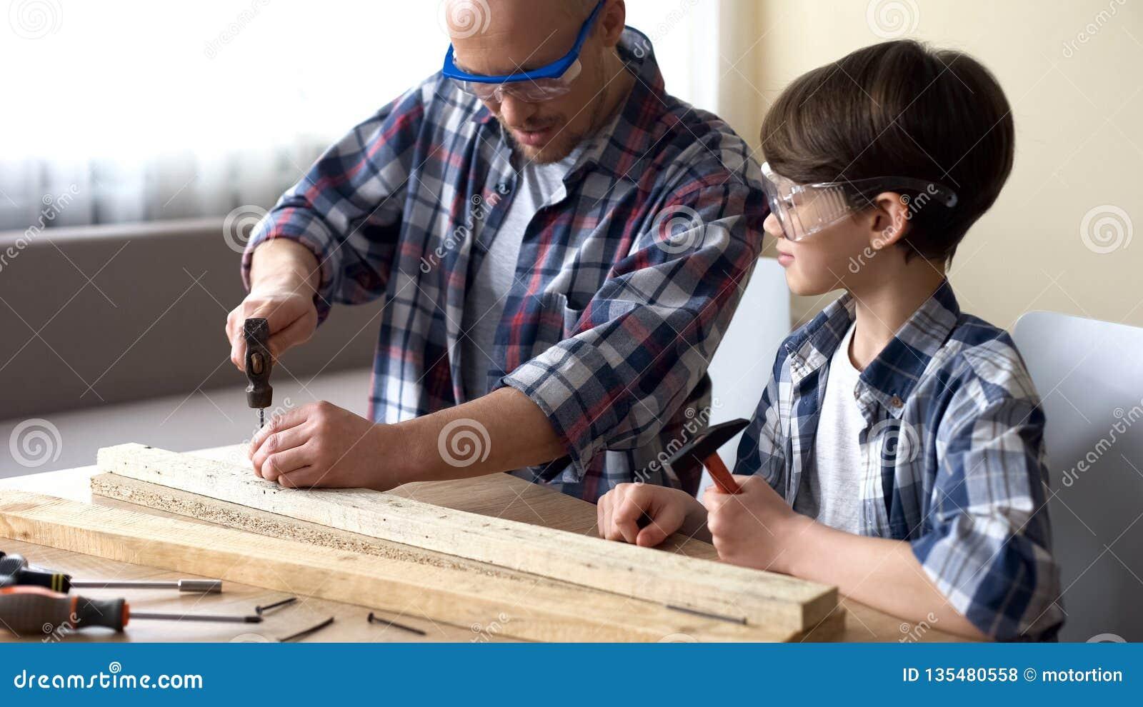 Μπαμπάς που διδάσκει λίγο γιο πώς να χρησιμοποιήσει το σφυρί ακίνδυνα, τον οικογενειακό ελεύθερο χρόνο, το χόμπι και τη διασκέδασ