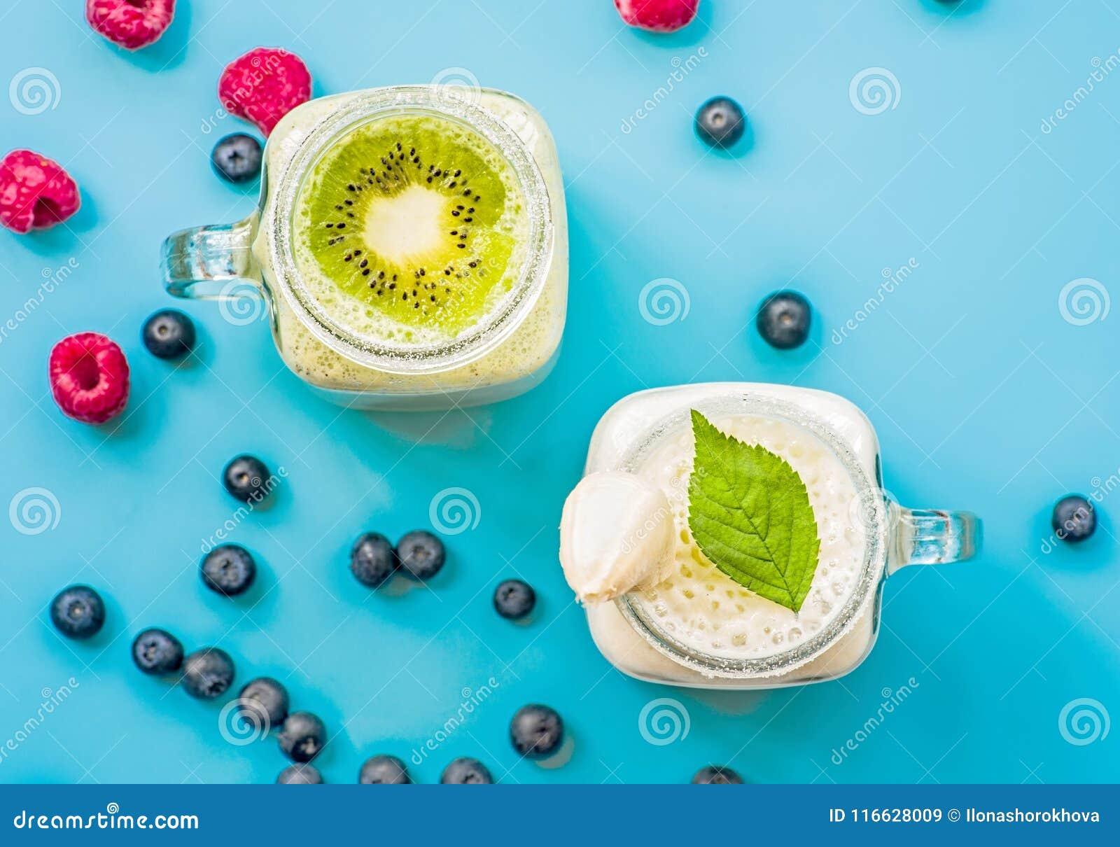 Μπανάνα δύο και ακτινίδιο milkshakes στα βάζα κτιστών με creme στην κορυφή που διακοσμείται με τα σμέουρα και τα βακκίνια επίπεδο