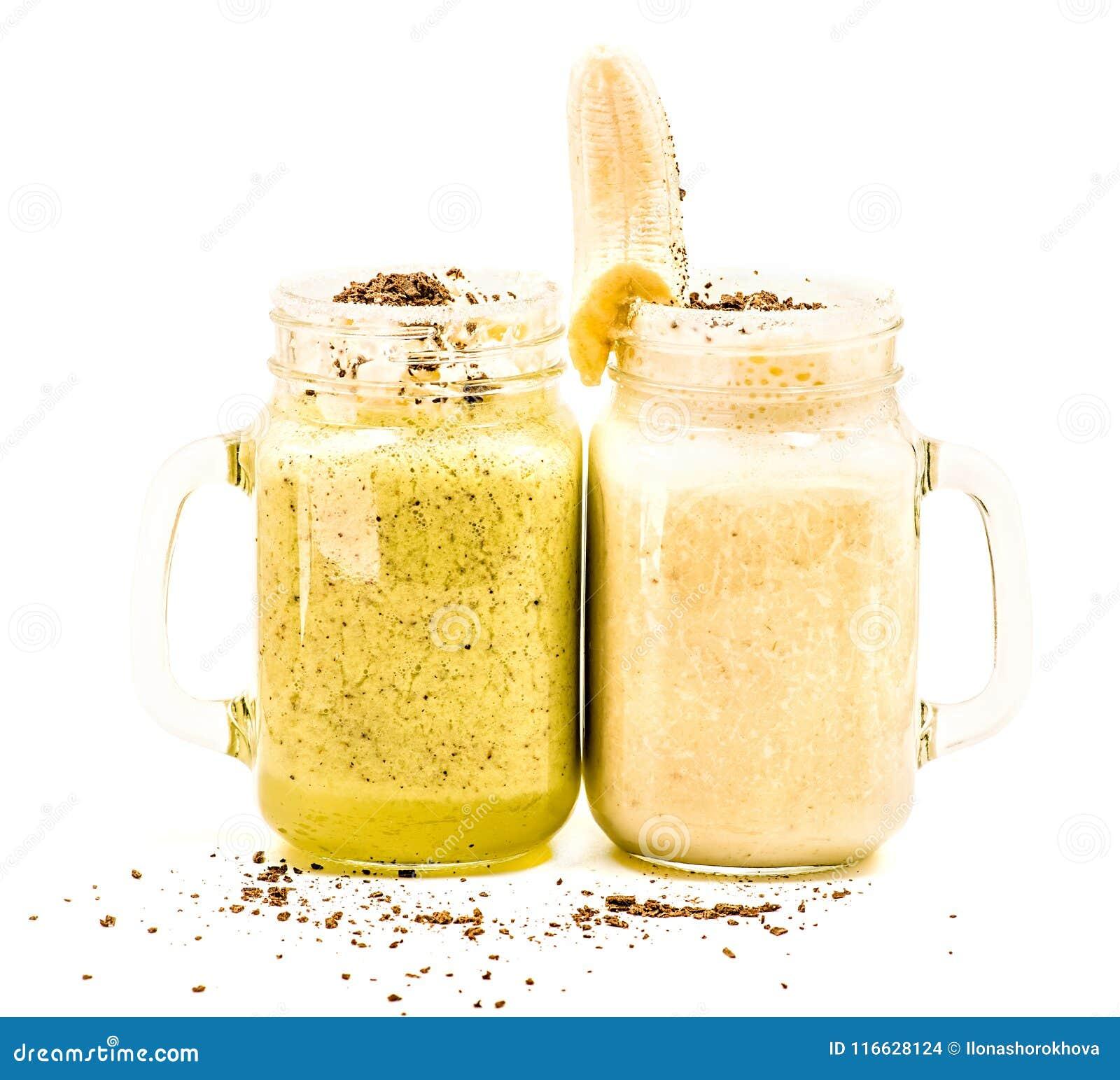 Μπανάνα και ακτινίδιο milkshakes στα βάζα κτιστών με creme και τη σοκολάτα στην κορυφή που διακοσμείται με την μπανάνα που απομον