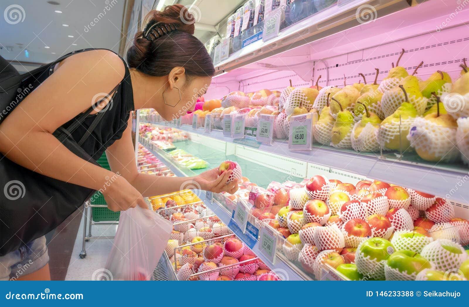 ΜΠΑΝΓΚΟΚ, ΤΑΪΛΑΝΔΗ - 28 ΑΠΡΙΛΊΟΥ: Απροσδιόριστος θηλυκά καταστήματα πελατών για τα μήλα στην υπεραγορά Foodland στη Μπανγκόκ στις