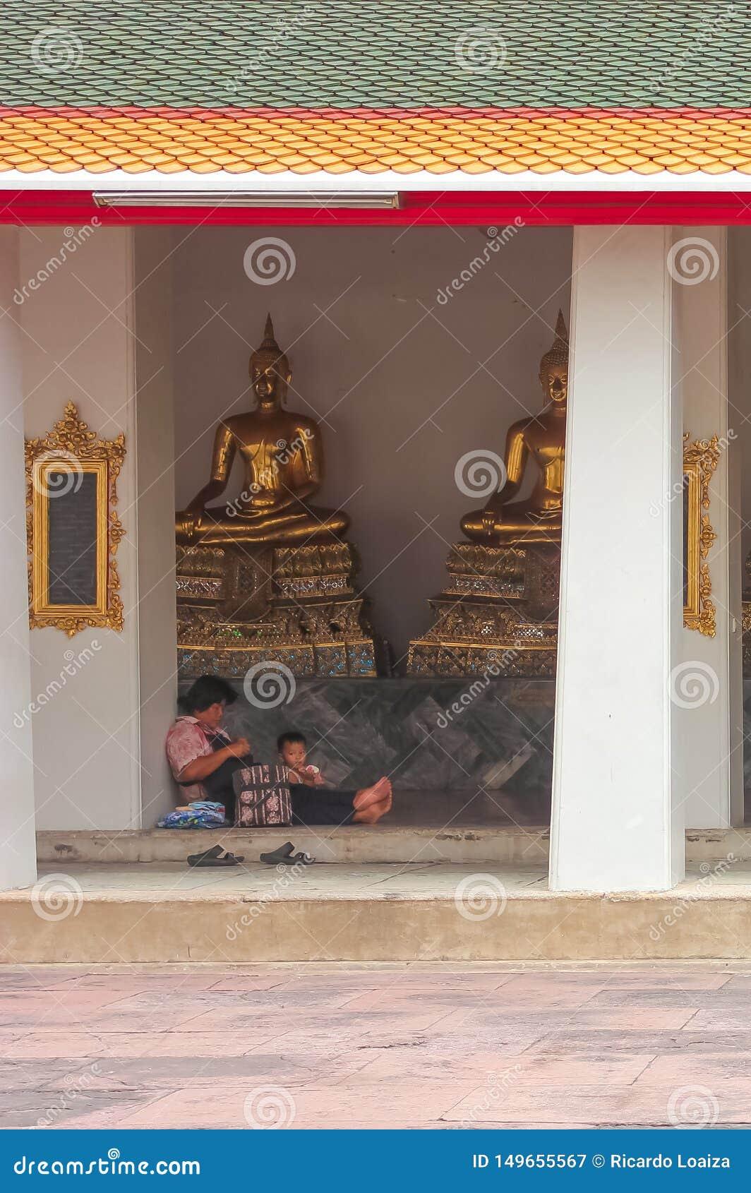 Μπανγκόκ, Ταϊλάνδη - 29 Απριλίου 2014 Συνεδρίαση μητέρων και γιων μπροστά από τα χρυσά γλυπτά του Βούδα σε Wat Pho, Ταϊλάνδη