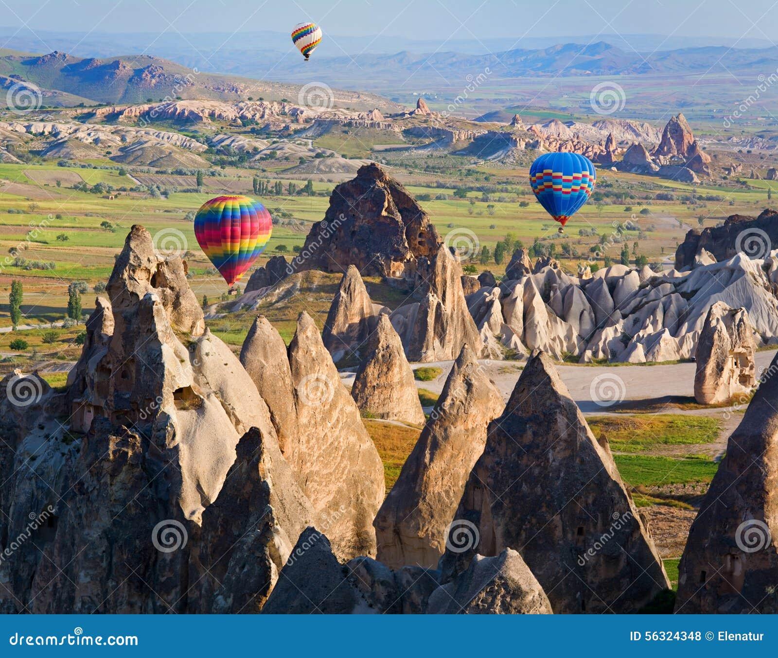 Μπαλόνι ζεστού αέρα που πετά πέρα από το τοπίο βράχου σε Cappadocia, Τουρκία