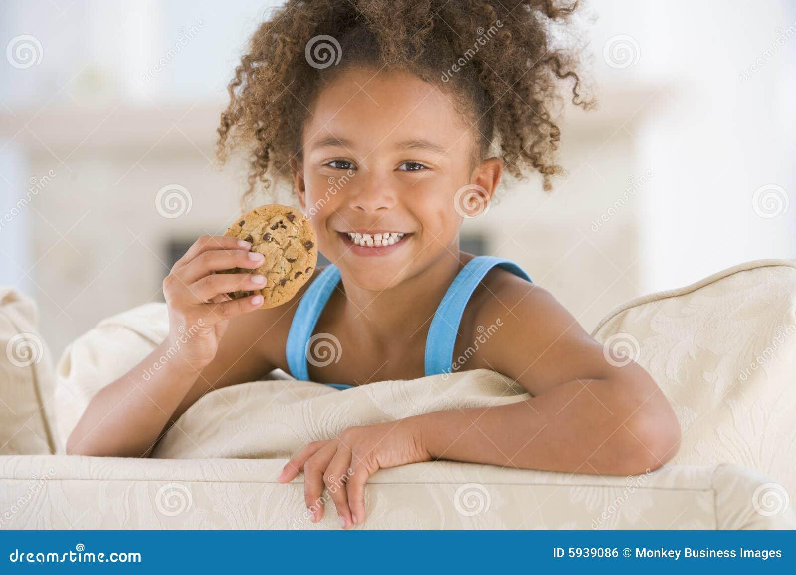 μπισκότο που τρώει τις χαμογελώντας νεολαίες καθιστικών κοριτσιών