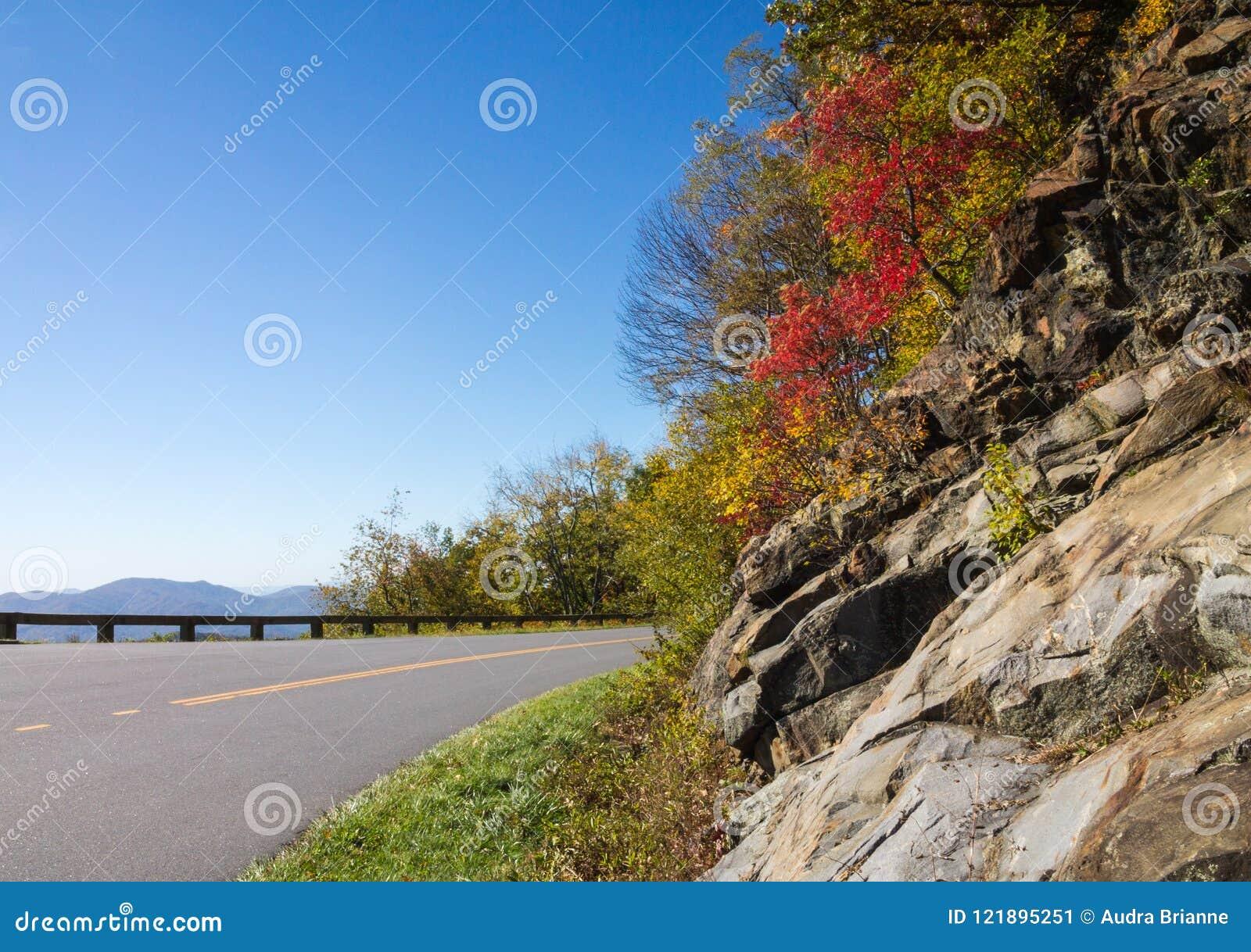 Μπλε θέα βουνού χώρων στάθμευσης κορυφογραμμών με το φύλλωμα που προσκολλάται στον ώμο