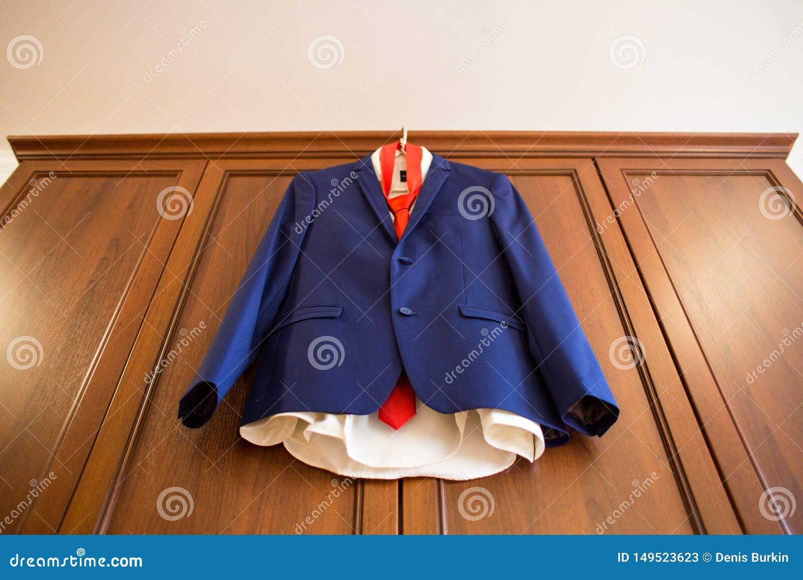 Μπλε κοστούμι νεόνυμφων με τον κόκκινο δεσμό που κρεμά το ξύλινο γραφείο Το πρωί του νεόνυμφου