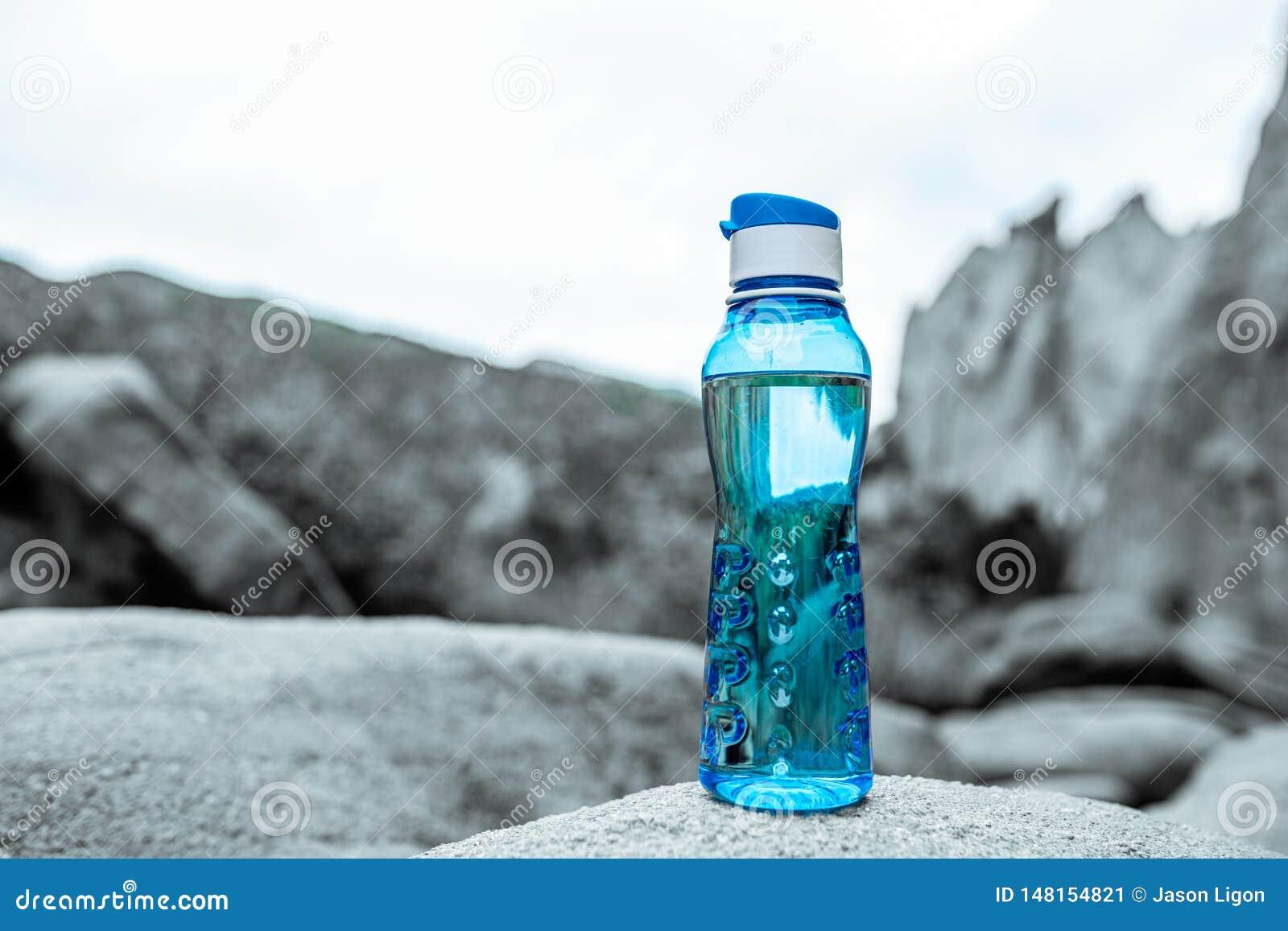 Μπλε μπουκάλι νερό ικανότητας Aqua με τα βουνά στο υπόβαθρο