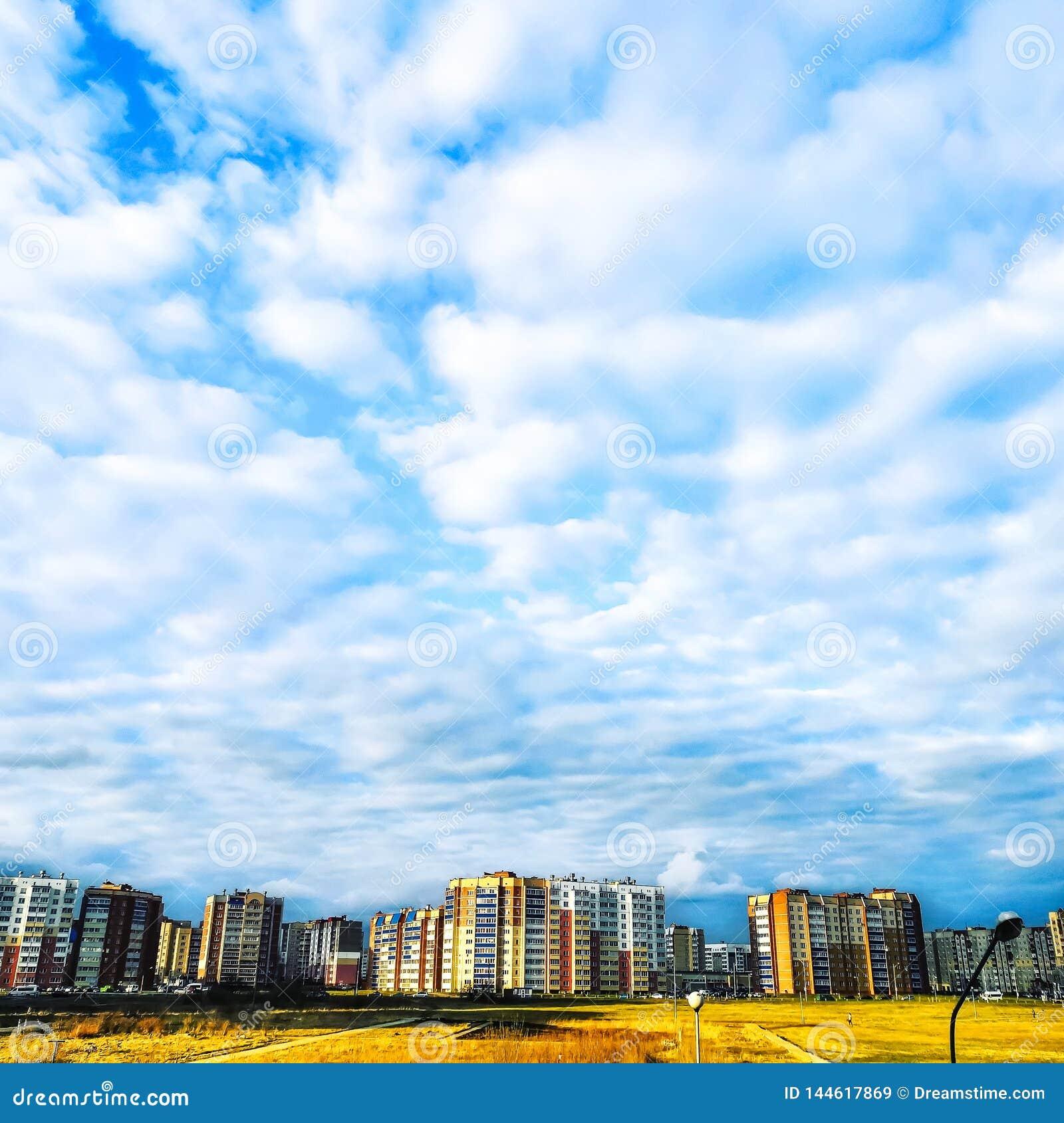 Μπλε ουρανός με τα άσπρα σύννεφα και τα κατοικημένα κτήρια στον ορίζον