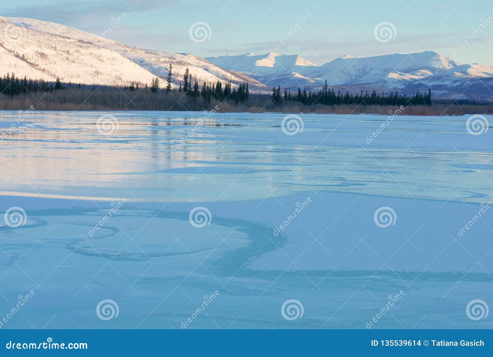 Μπλε πάγος της παγωμένης λίμνης στο πρωί Χειμερινό τοπίο στα βουνά και ο χειμερινός δρόμος στο Γιακουτία, Σιβηρία, Ρωσία