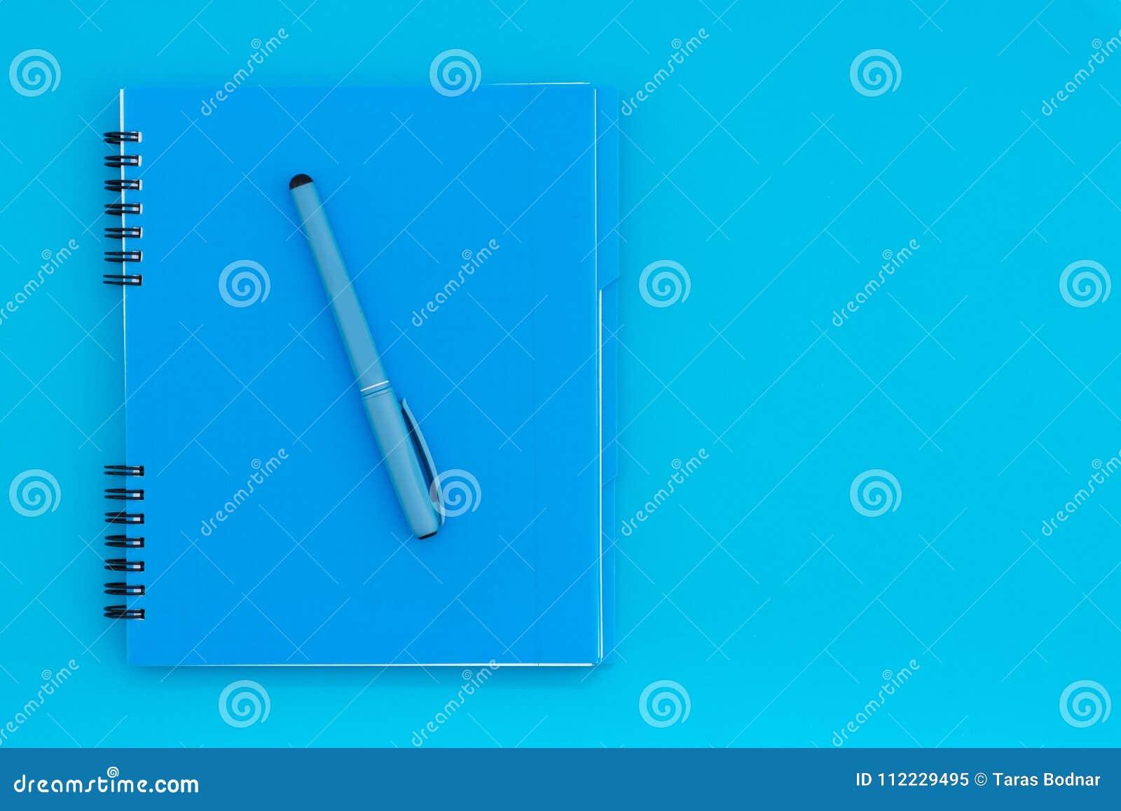 Μπλε σημειωματάριο με ένα μολύβι σε ένα μπλε υπόβαθρο Επίπεδος βάλτε το πρότυπο τοποθετήστε το κείμενο