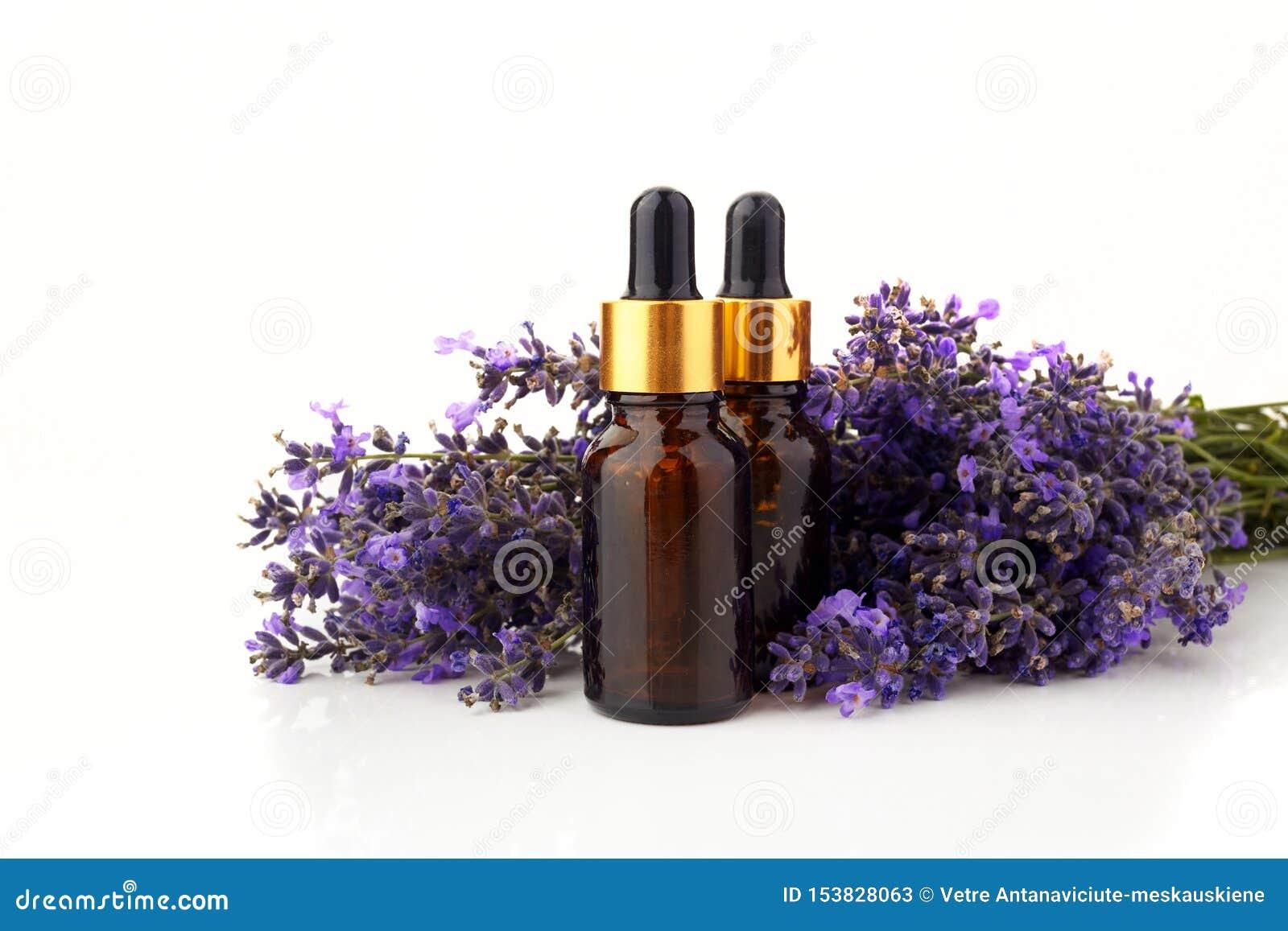 Μπουκάλια με ελαίου και lavender αρώματος τα λουλούδια που απομονώνονται στο λευκό