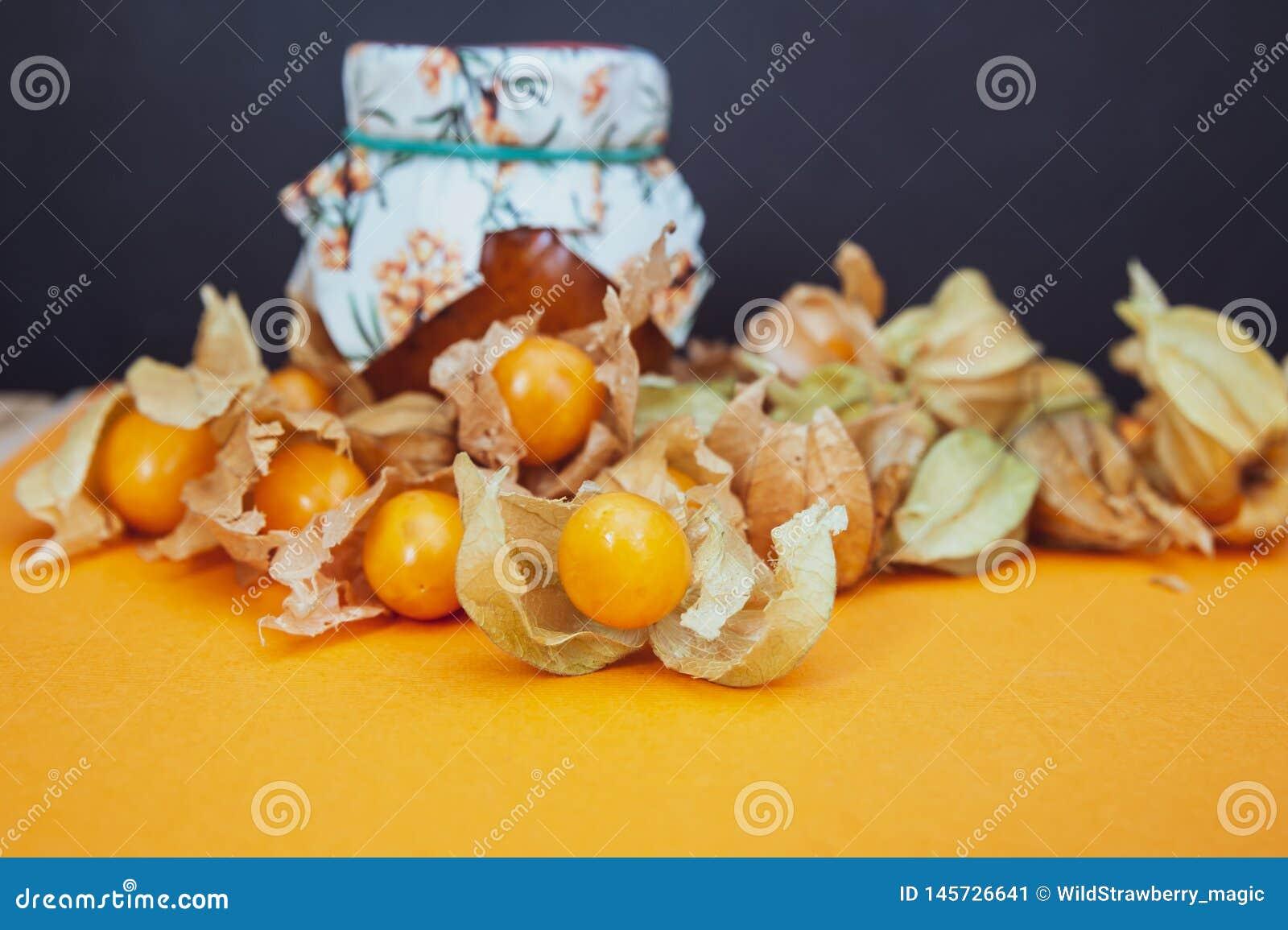 Μπουκάλια με τη μαρμελάδα physalis και τους νωπούς καρπούς στο πορτοκάλι