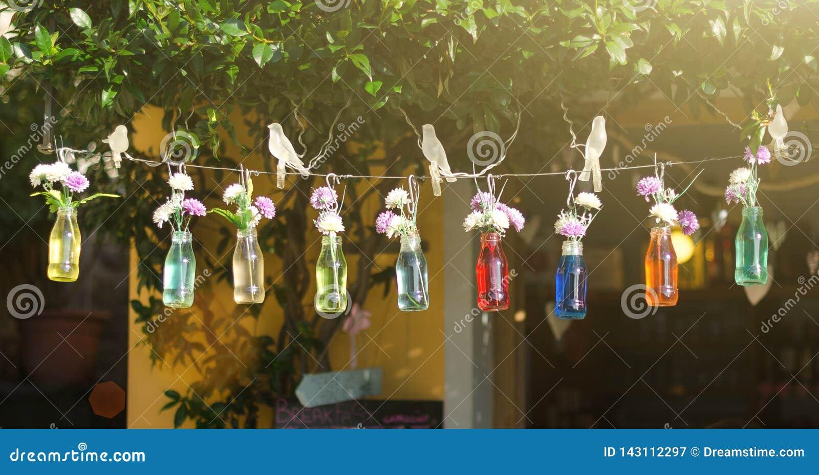 Μπουκάλια με το χρωματισμένο νερό και λουλούδια που κρεμούν σε μια σειρά στο υπόβαθρο θερινών οδών