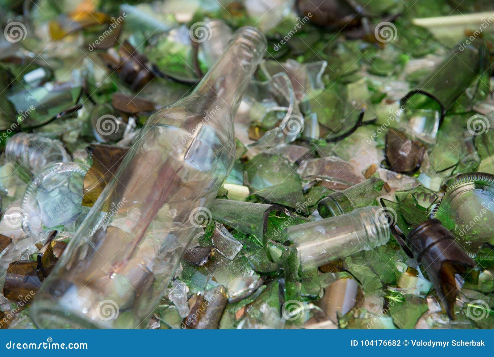Μπουκάλι κρασιού που βρίσκεται σε ένα κρεβάτι του διαφυγής του σπασμένου γυαλιού το θραυστήρα σε μια δυνατότητα ανακύκλωσης