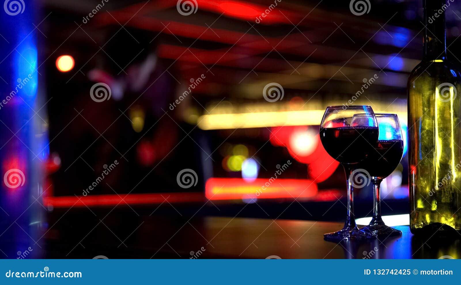 Μπουκάλι του κρασιού με δύο γυαλιά, φιλώντας νέο ζεύγος στο θολωμένο υπόβαθρο