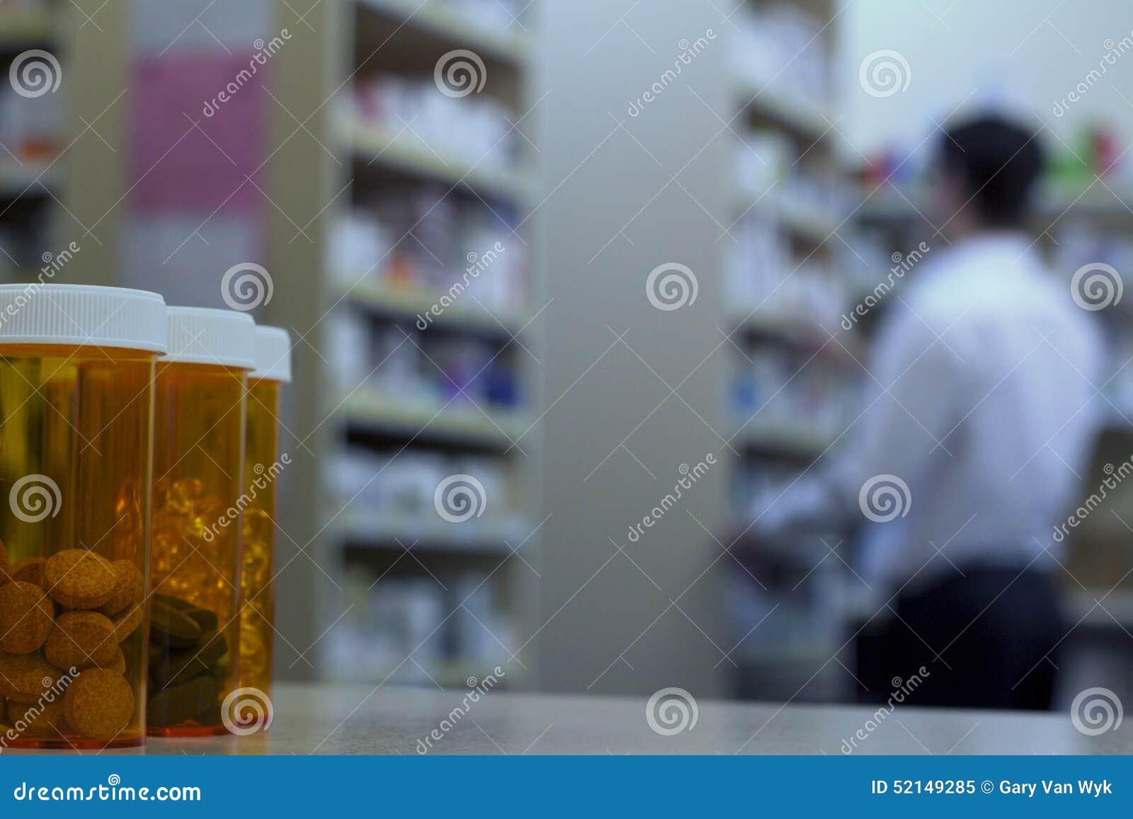 Μπουκάλια χαπιών σε έναν μετρητή φαρμακείων με το φαρμακοποιό στο υπόβαθρο